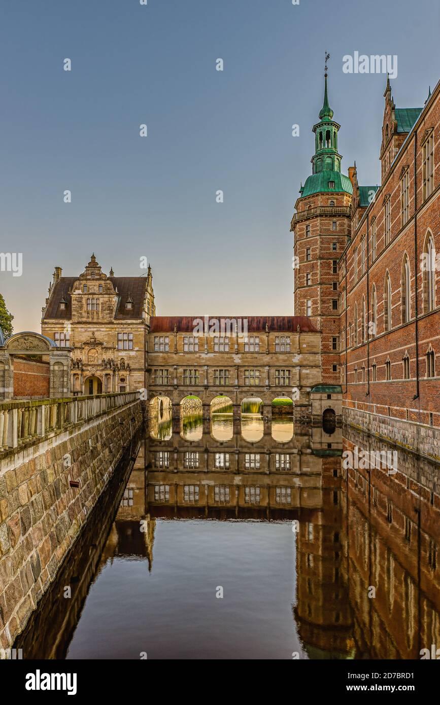 El castillo de Frederiksborg y el puente sobre el foso se reflejan en el agua brillante una mañana temprano en el amanecer, Hillerod, Dinamarca, 17 de octubre de 2020 Foto de stock