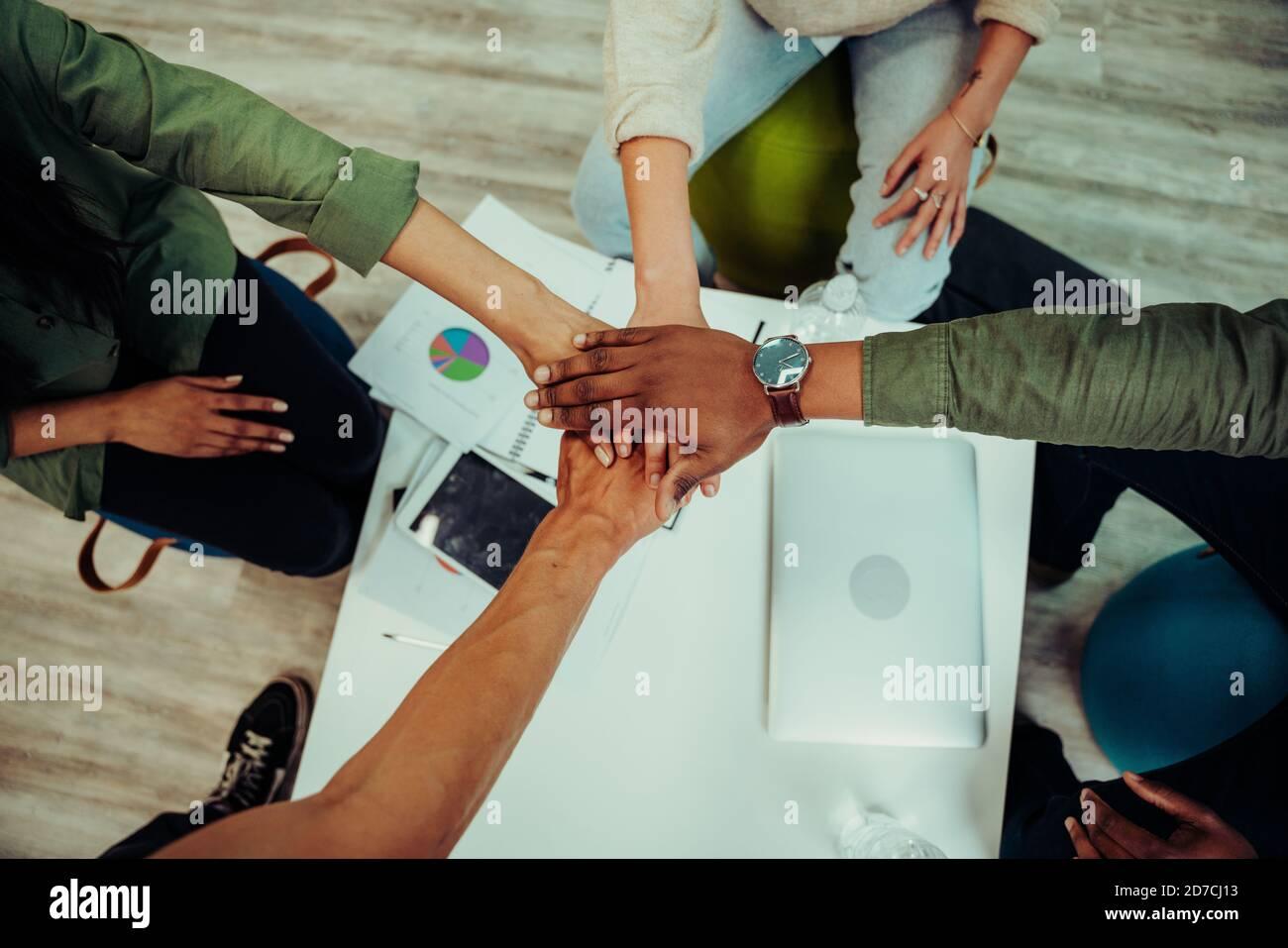 Compañeros de negocios apilando las manos juntos creando la unidad del equipo preparándose para presentación al jefe y gerentes Foto de stock