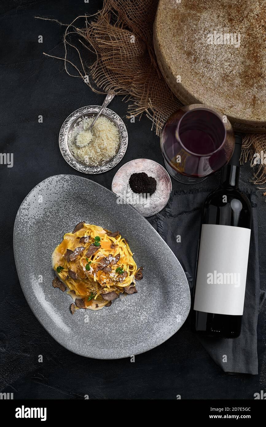 Cocina italiana - espaguetis con trufa negra en un plato gris y una botella de vino. Enfoque selectivo. Vertical. Foto de stock