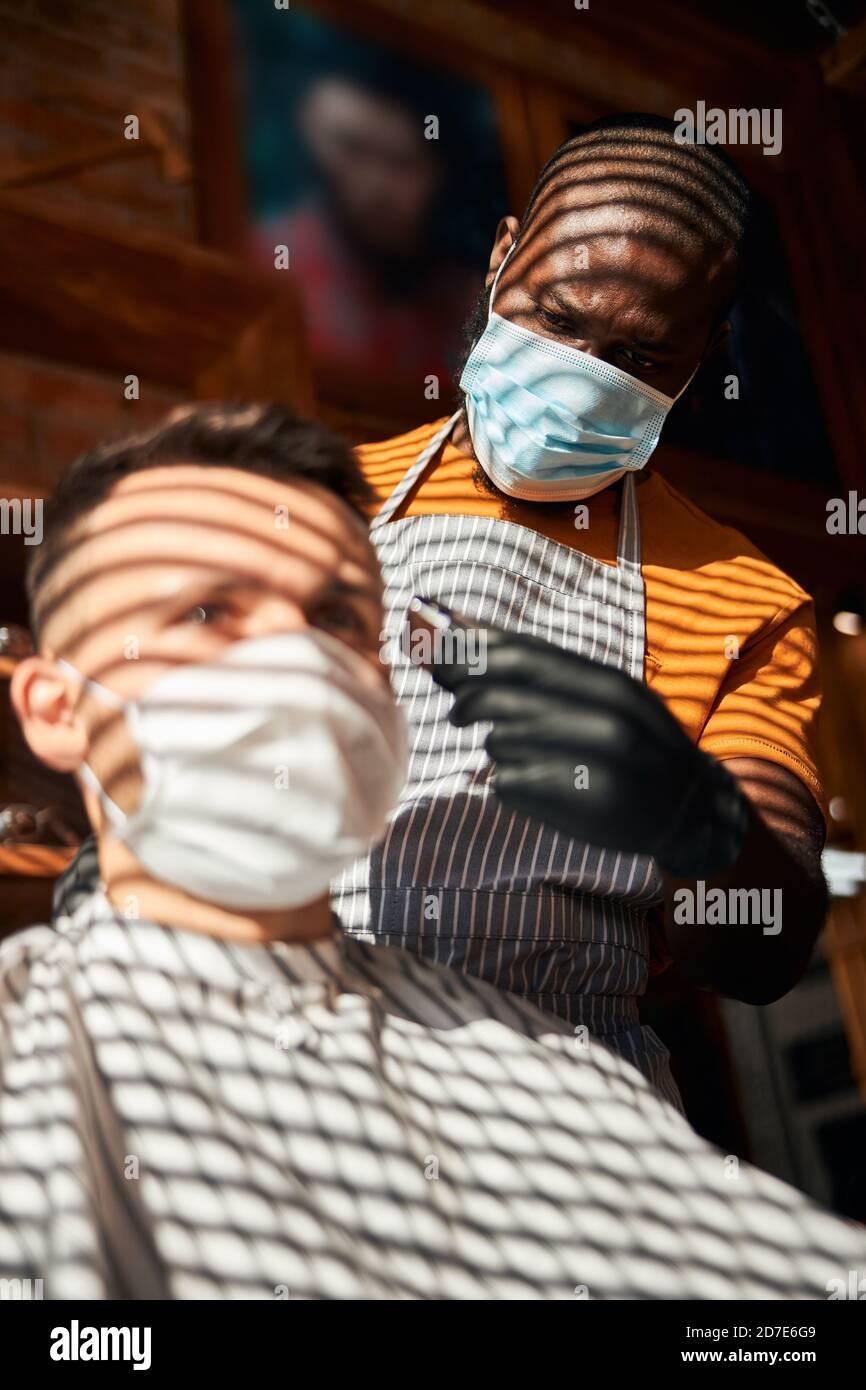 Barbería en máscara médica cortando el cabello de los clientes en la peluquería Foto de stock