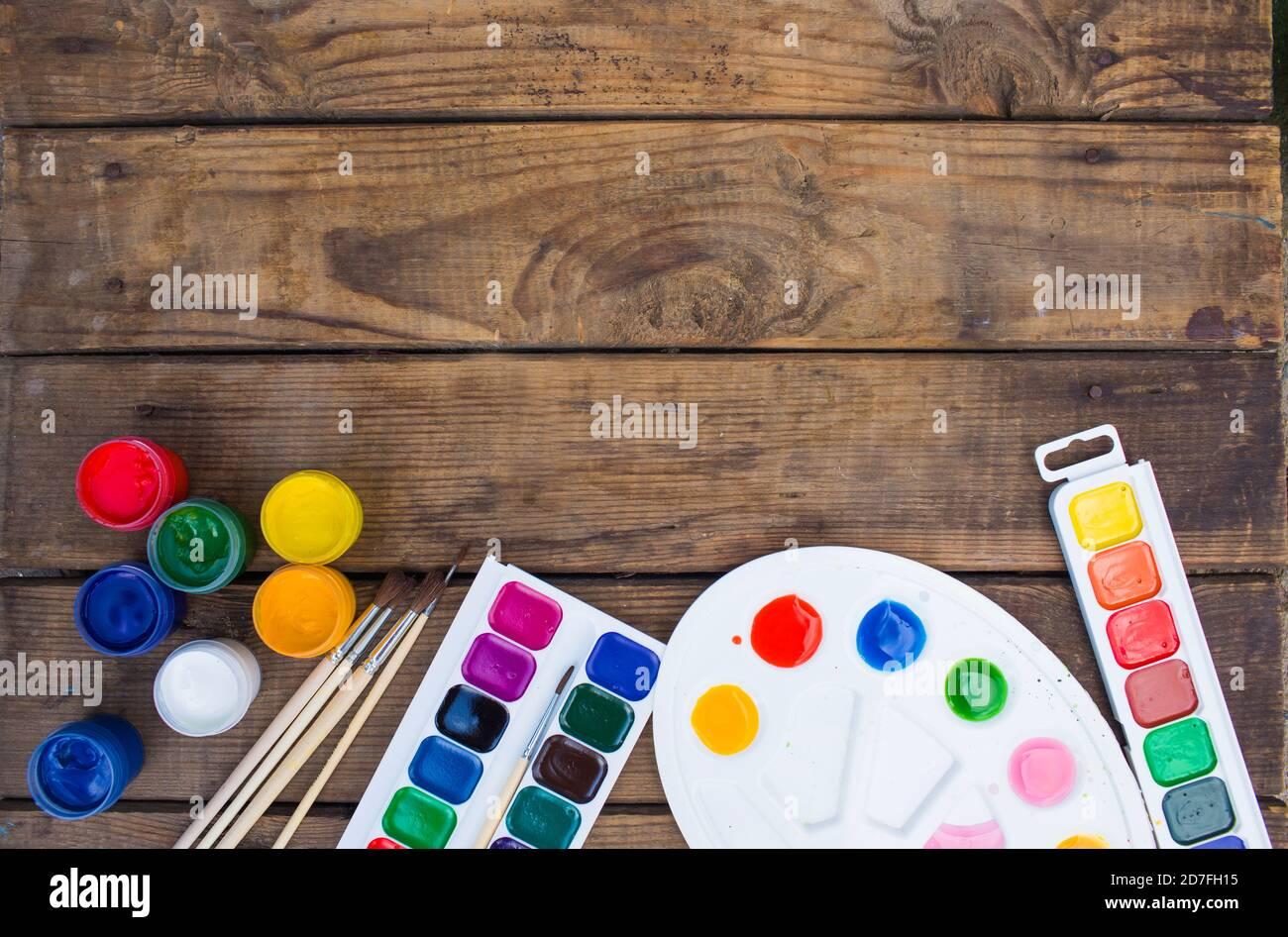 pinturas multicolor, paleta de pinceles, pincel, yacen en una vista superior de fondo de madera Foto de stock