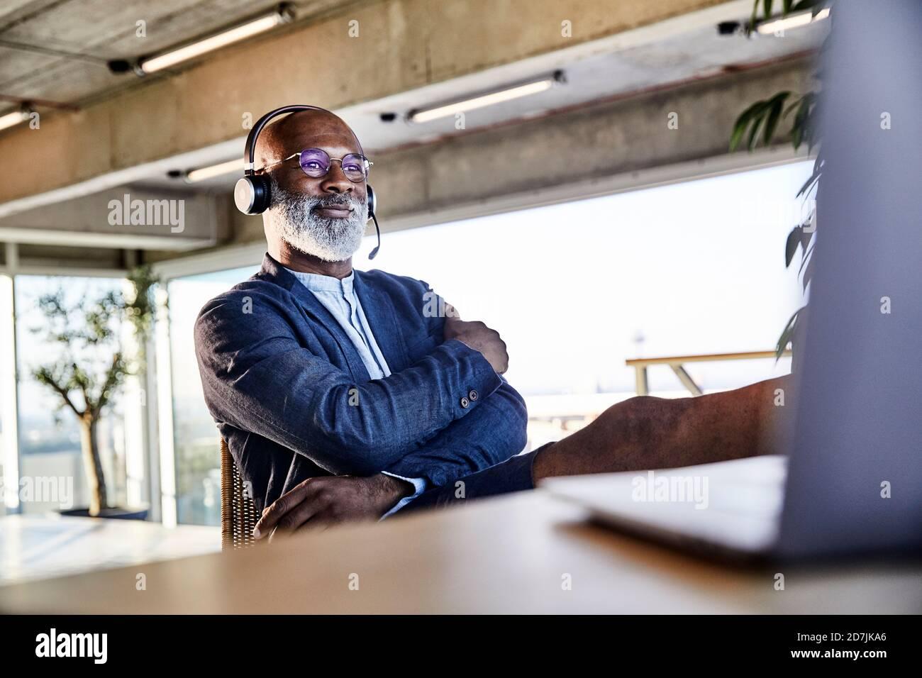 Hombre maduro con los brazos cruzados concentrándose mientras trabajaba en el ordenador portátil Foto de stock