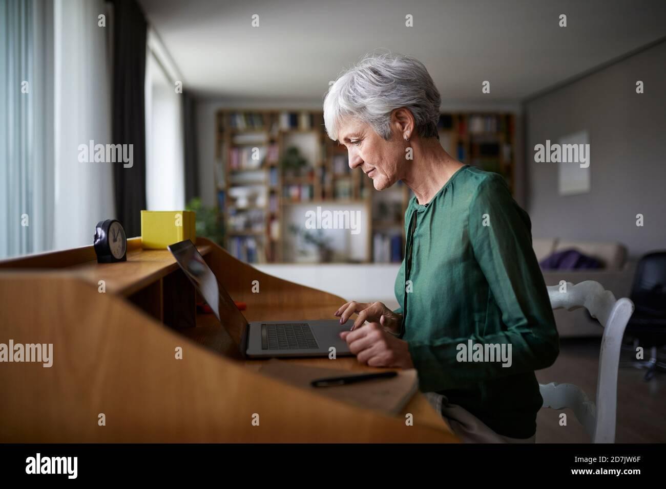 Mujer mayor activa que se concentra mientras trabaja en el ordenador portátil Foto de stock
