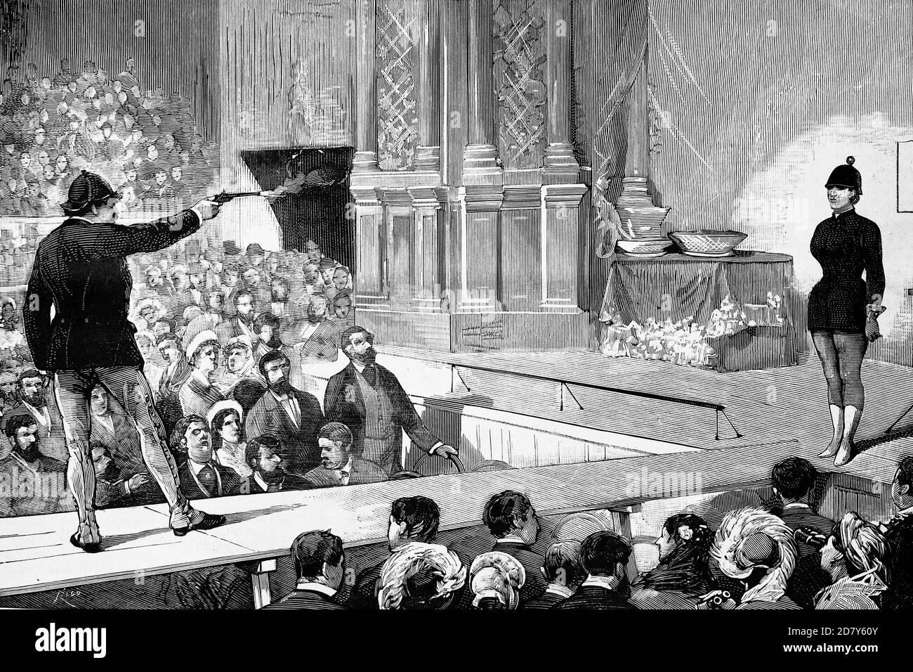 Madrid, España, Circus Price, el shooter estadounidense Paine ejecutando sus arriesgados ejercicios con su esposa como asistente. Ilustración antigua. 1882. Foto de stock