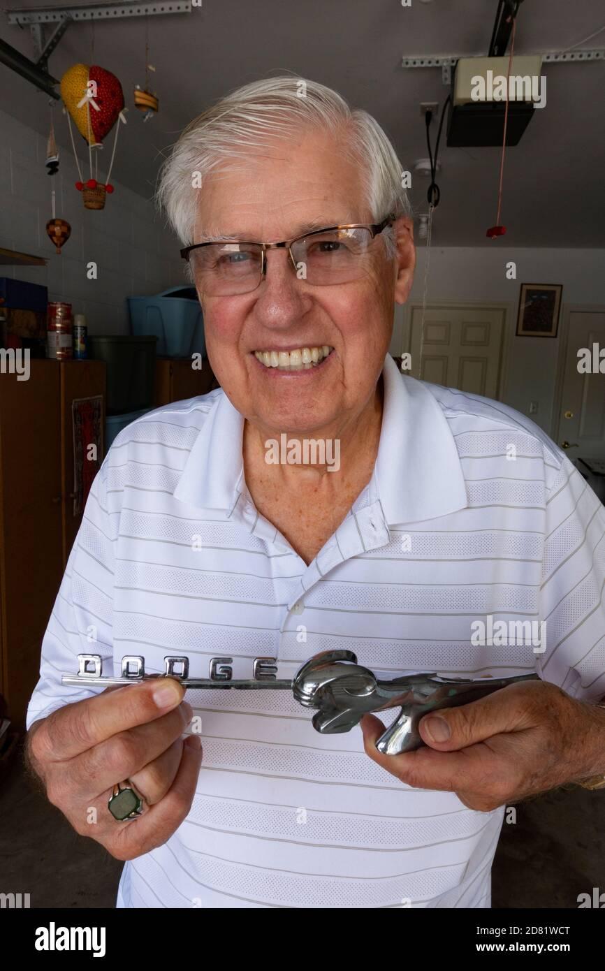 Guapo caballero mayor sosteniendo la letra de cromo Dodge y el ornamento de la capucha de su primer coche. Downers Grove Illinois IL EE.UU Foto de stock