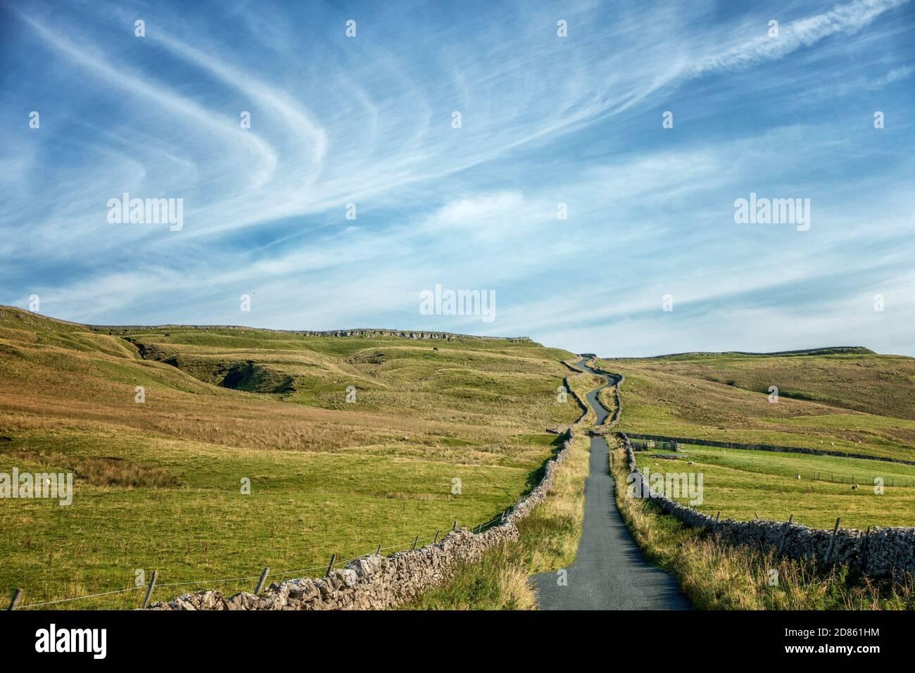 Cielos con plumas y sol en la cima de la famosa subida en bicicleta de la colina, Park Rash, tranquilo carril de campo fuera de Kettlewell. Wharfedale, Yorkshire del Norte Foto de stock
