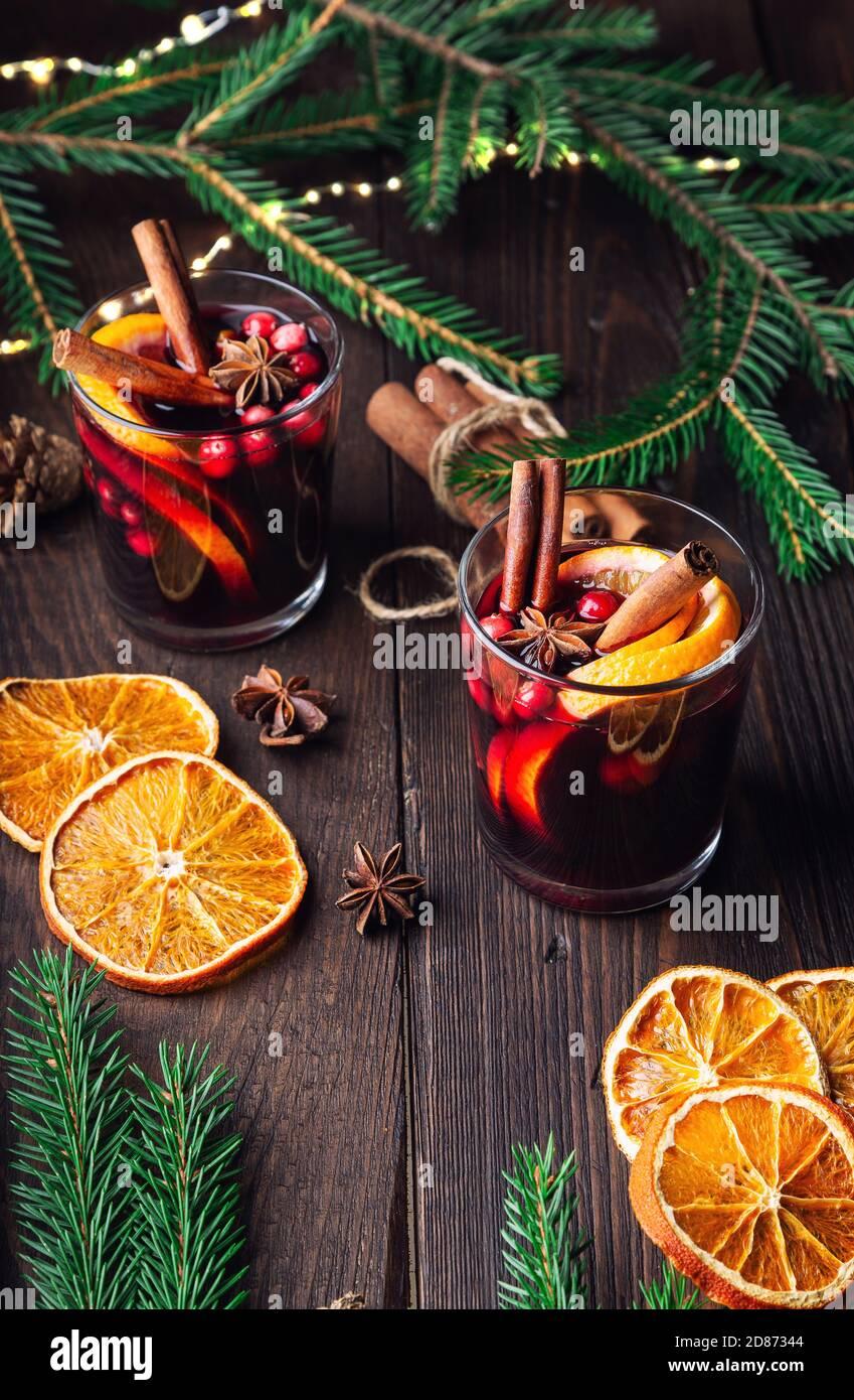 Vino de Navidad con arándanos, naranja y especias sobre fondo rústico de madera. Bebida tradicional caliente de invierno. Foto de stock