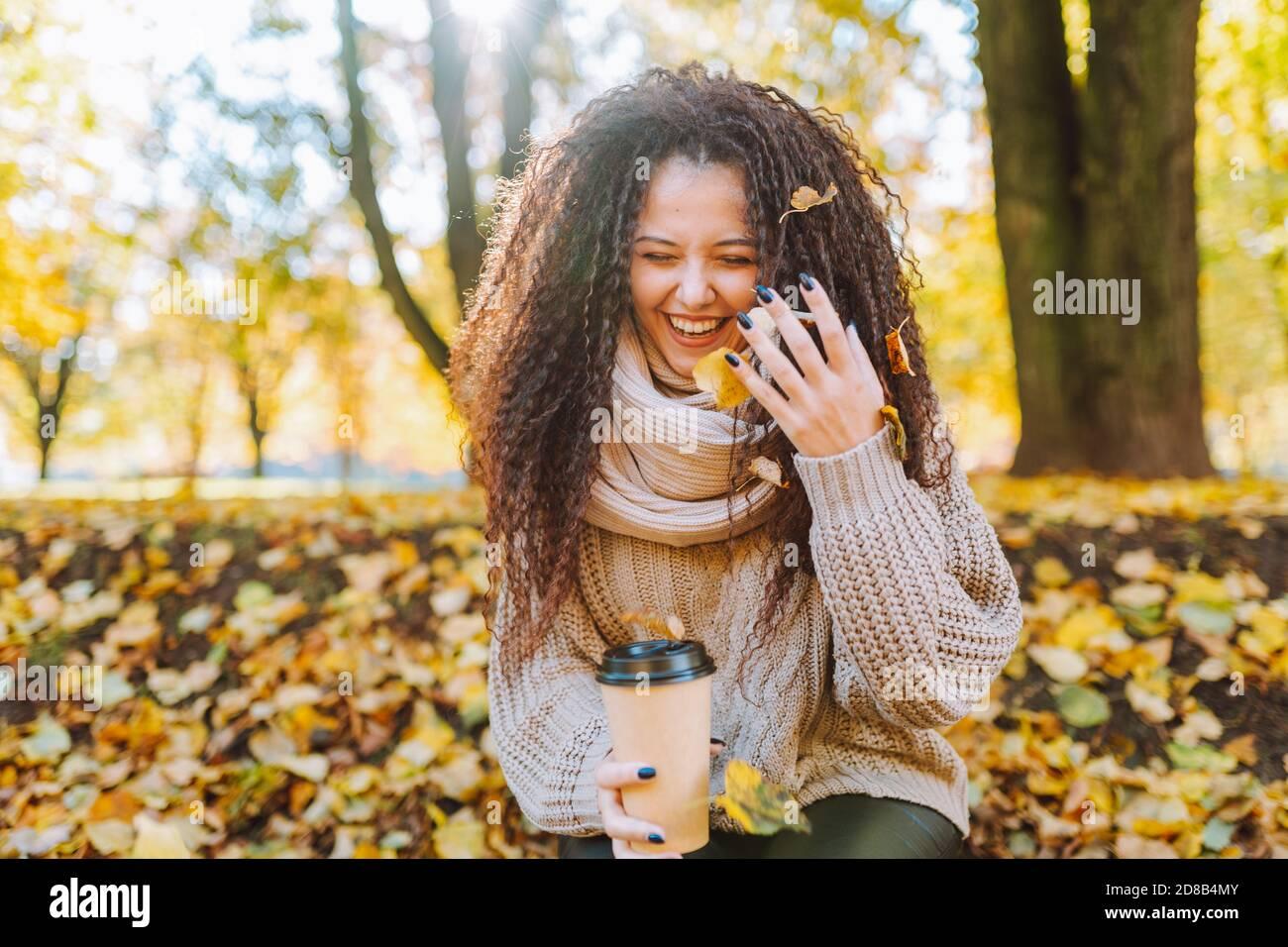 Positivo afro cabello mujer con hermosa sonrisa usando Jersey de punto y la bufanda tiran hojas amarillas de otoño en el parque al sol día Foto de stock