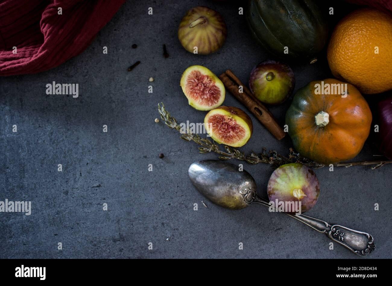 Frutas y verduras frescas en una mesa. Gema de calabaza, ciruelas, higos y cuchara de plata sobre fondo gris. Foto superior de la cosecha de otoño. Foto de stock