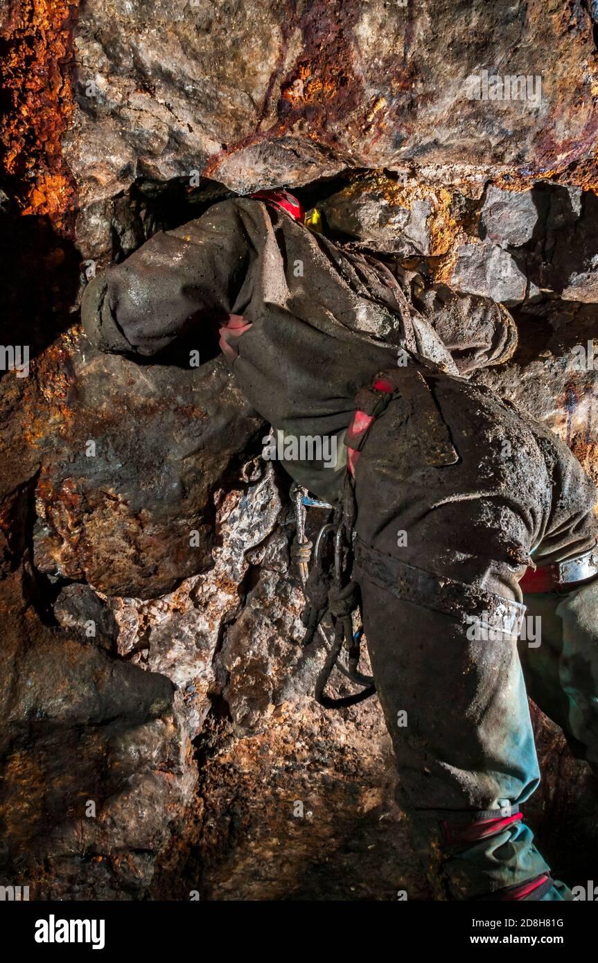 """Mirando a través de una pequeña ventana de ventilación o """"thurl"""" entre dos venas minerales estrechamente paralelas en Odin Mine, Castleton, Derbyshire. Foto de stock"""