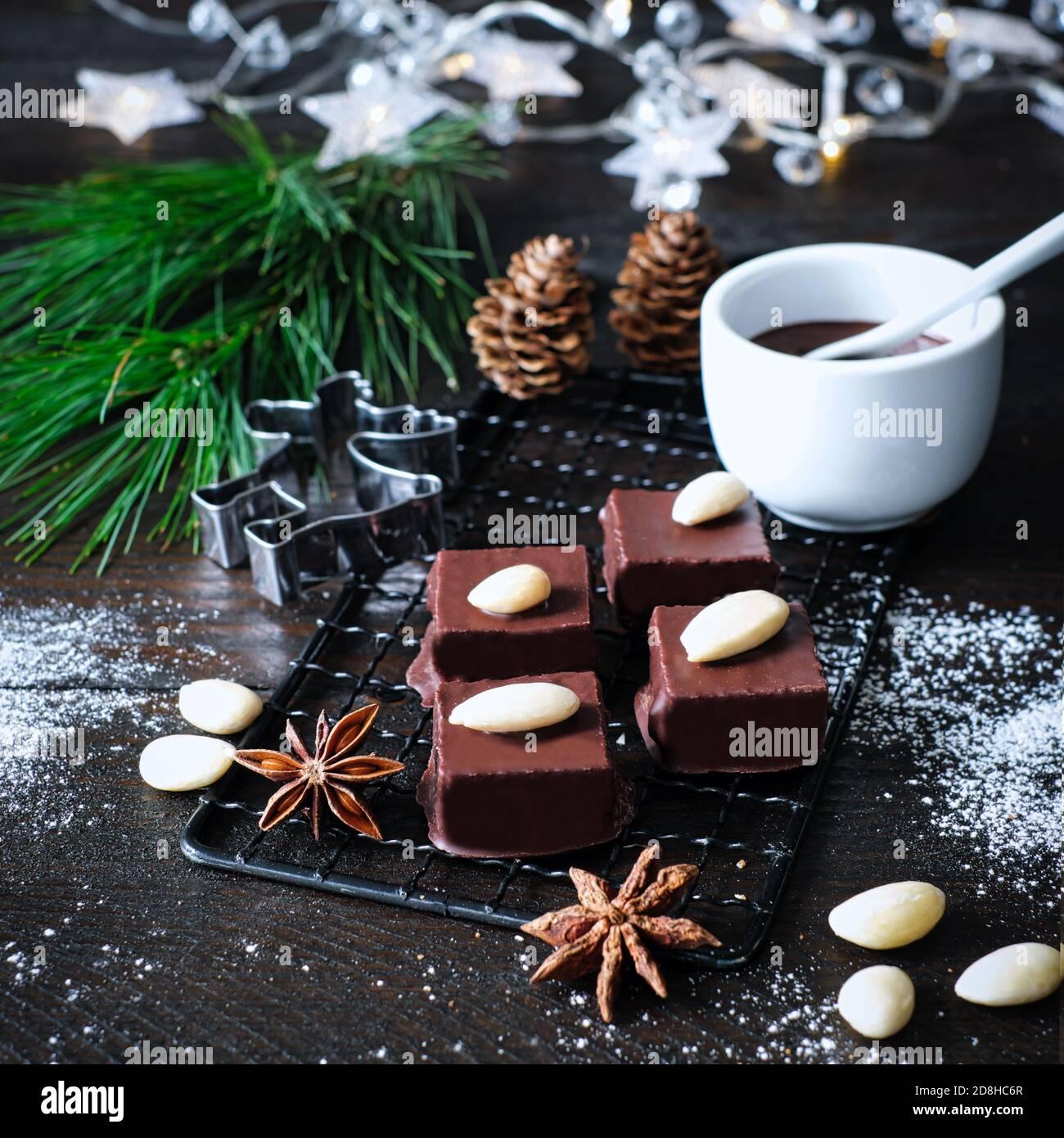 Marzipancubes con helado de chocolate en una rejilla de enfriamiento negro, decorado con ramas de pino, bastones de canela y estrellas de anís, conos de abeto, junto a ella un arco Foto de stock