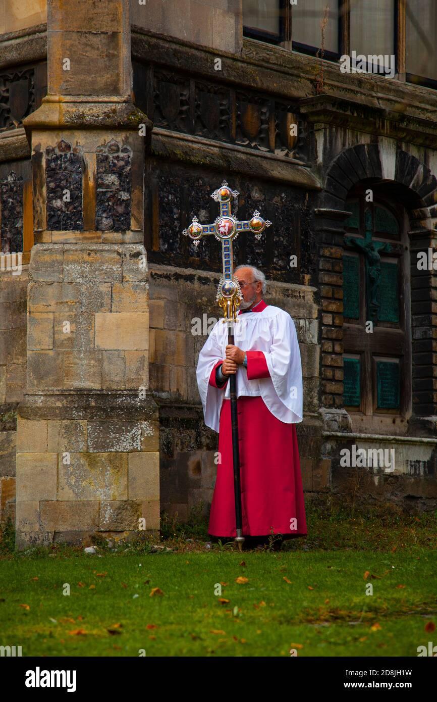 Norwich, Reino Unido 10/07/2012: Un sacerdote de iglesia anglicano en un manto rojo y blanco oeste se ve fuera de una iglesia histórica. Lleva una larga c decorativa Foto de stock