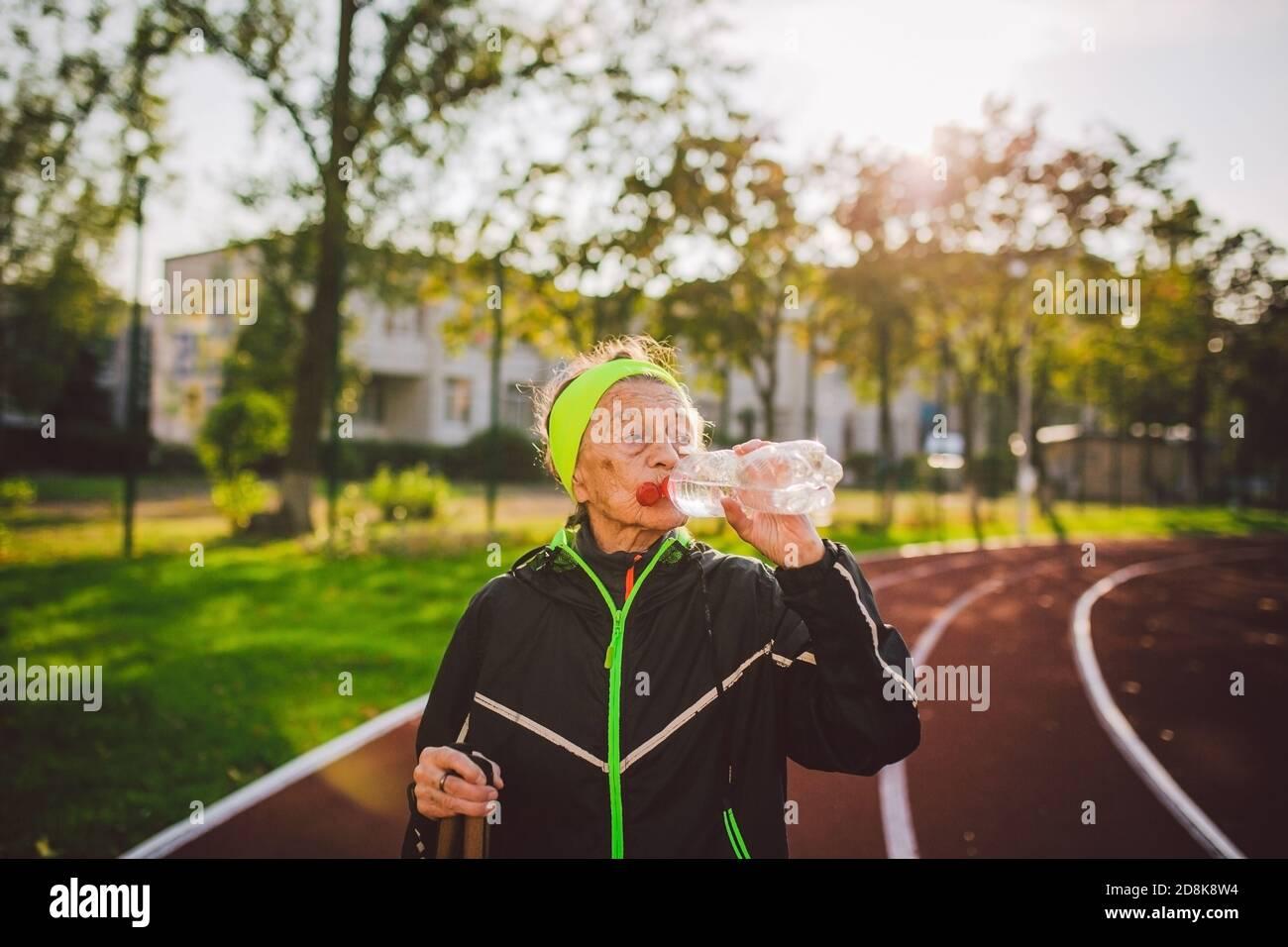 Mujer mayor practicando marcha nórdica en el estadio de la ciudad y se detuvo para saciar la sed, beber agua de la botella. Edad, madurez, estilo de vida activo y. Foto de stock