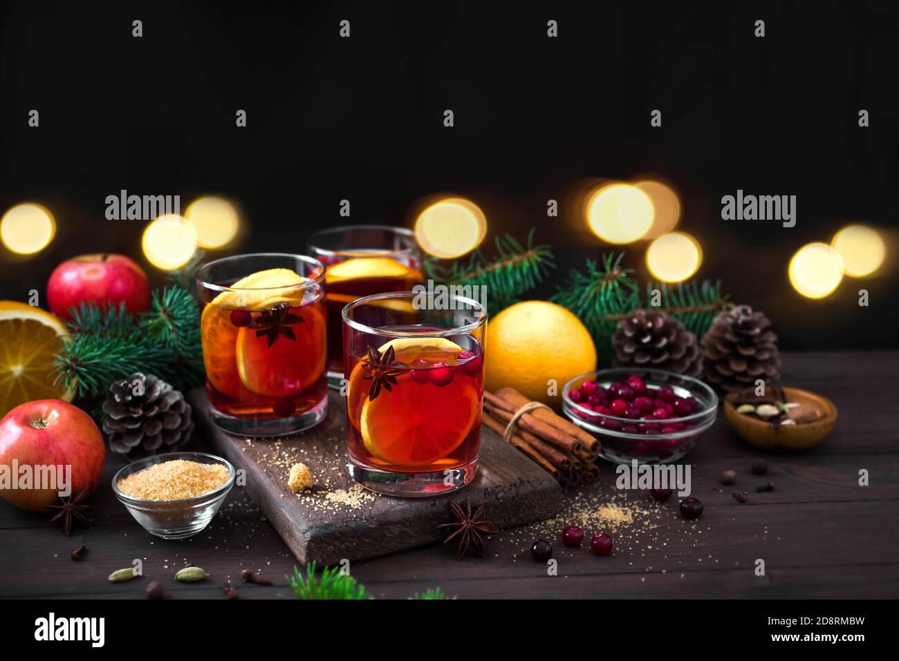 Vino tinto de Navidad con especias y naranjas sobre mesa rústica de madera. Bebida caliente tradicional para las vacaciones de Navidad e invierno. Foto de stock