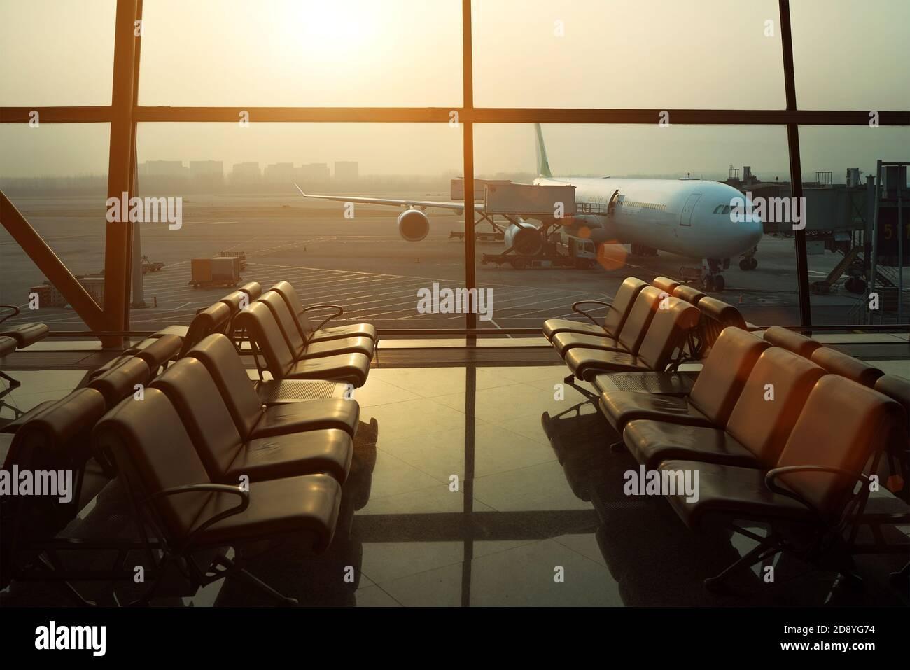 Preparación de vuelos de aviones - abastecimiento de combustible, catering, servicios de equipaje antes del despegue del avión. Zona de espera con sillas en la terminal del aeropuerto internacional Foto de stock