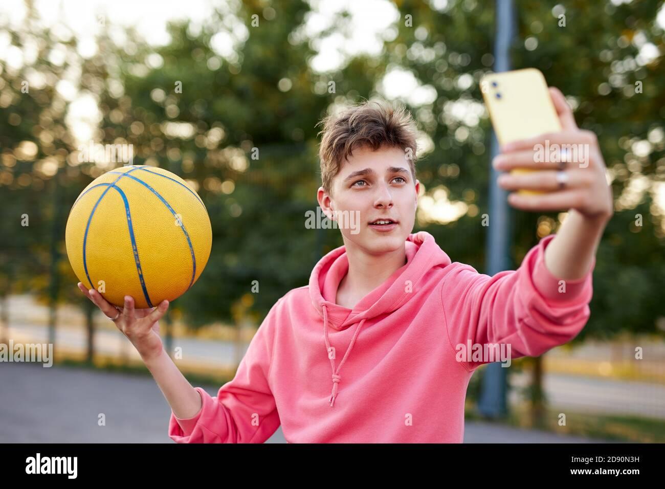joven basketballer caucásico tomar una foto de sí mismo con pelota, chico atlético mirar smartphone, posando Foto de stock