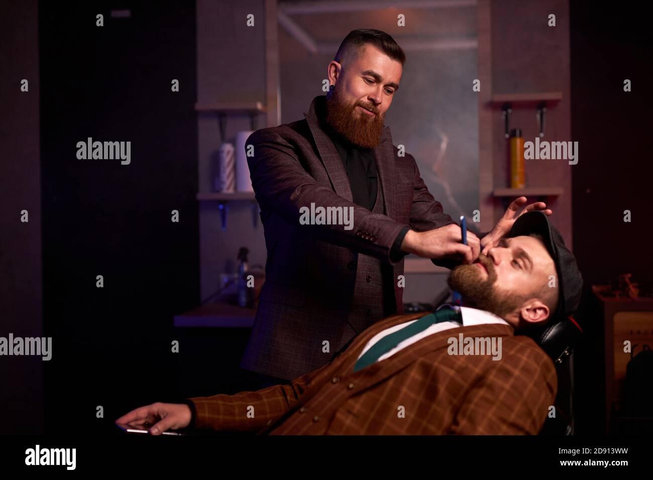 concepto de tienda de belleza para hombres. peluquería profesional afeitando la barba a los clientes ricos en una peluquería, cortes de pelo brutales Foto de stock