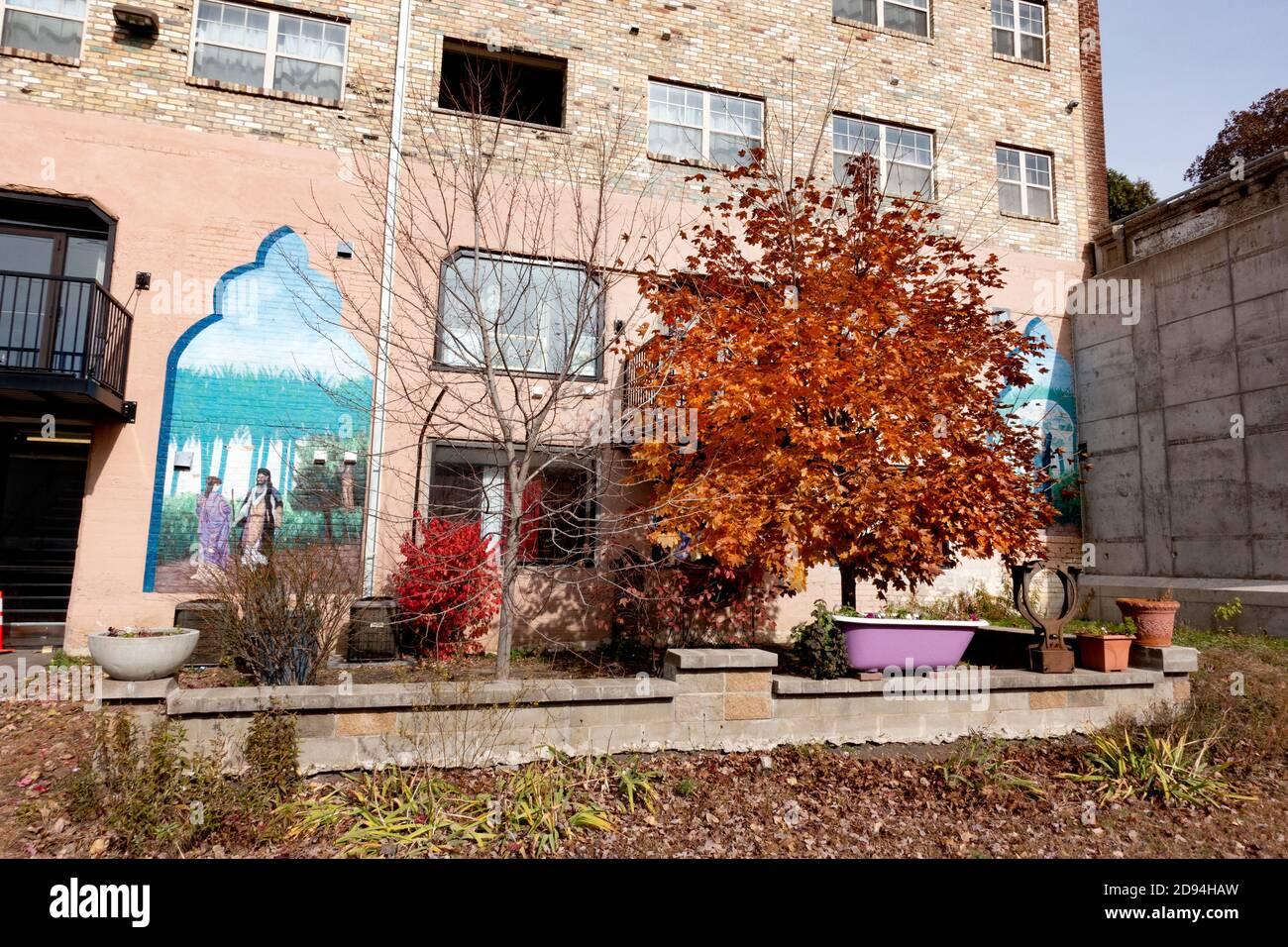 Edificio de apartamentos Mideast con un patio decorado y un hermoso árbol de otoño situado junto al sendero Midtown Greenway. Minneapolis Minnesota MN EE.UU Foto de stock