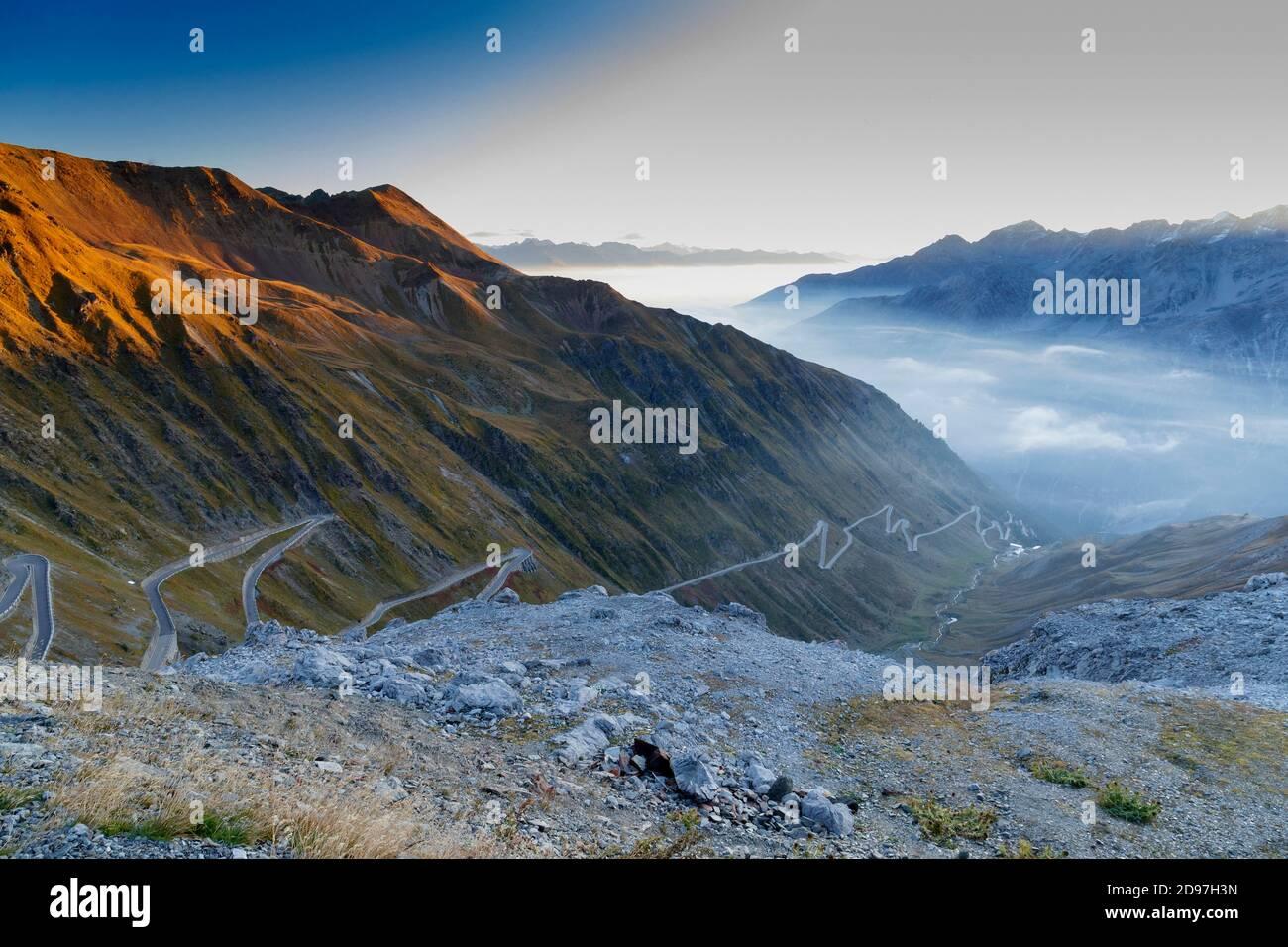 Paso de Stelvio con montañas cubiertas de nieve y una sinuosa carretera en el valle, Trentino-Alto Adige, Italia Foto de stock