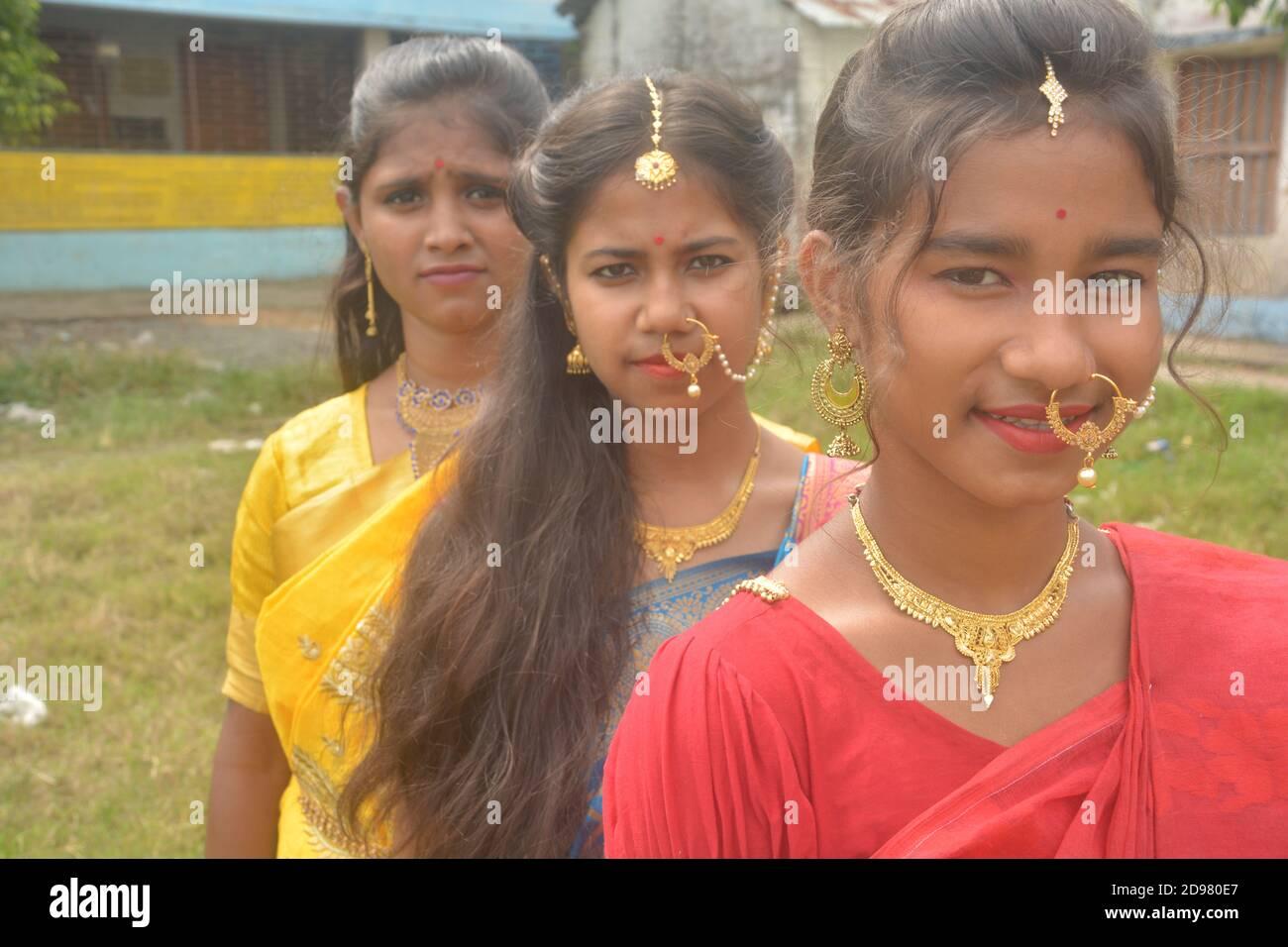 Primer plano de tres adolescentes indias con sari oro nariz anillo maang tikka collar pendientes con Maquillo, enfoque selectivo Foto de stock