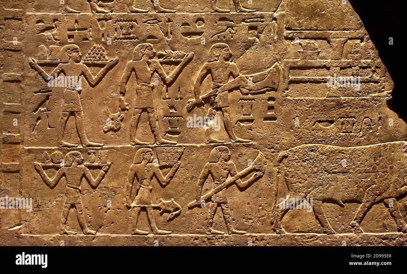Fragmento de pared de la tumba de Neferkhau y Satbahetep (las escenas están relacionadas con la comida funeraria.) El fallecido Neferkhau y una mujer llamada Satbahetep, el registro superior está reservado a los sacerdotes. Los otros tres registros muestran que los portadores que traen bienes para la ka del fallecido Satbahetep, durante el banquete funerario. 1ER PERÍODO INTERMEDIO 2181–2055 AC Egipto, egipcio. Foto de stock