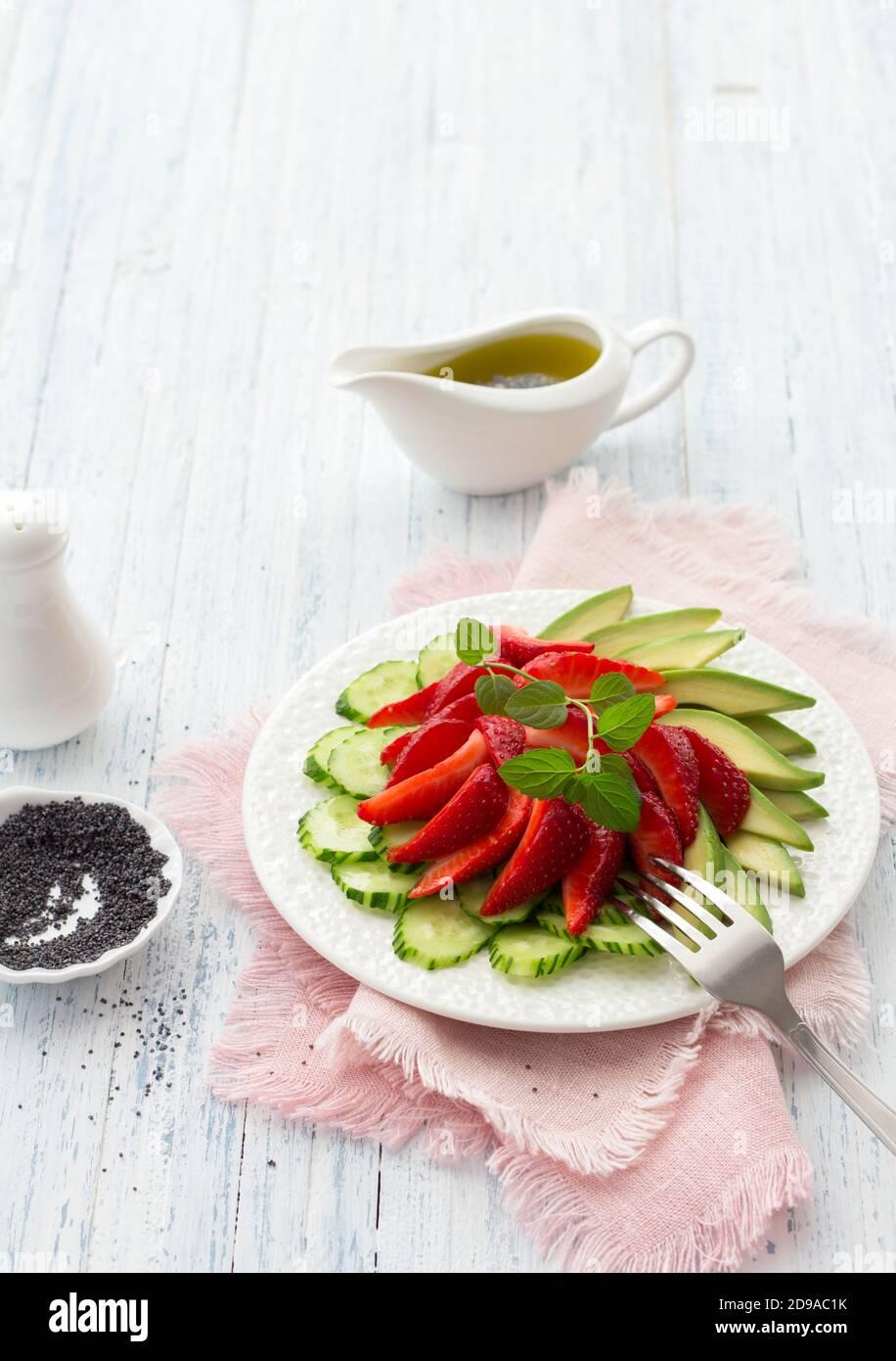 Ensalada vegana de fresa, pepino y aguacate con semillas de amapola, aderezo de aceite y menta. Alimentos frescos, saludables y dietéticos. En un plato blanco y en un blu Foto de stock