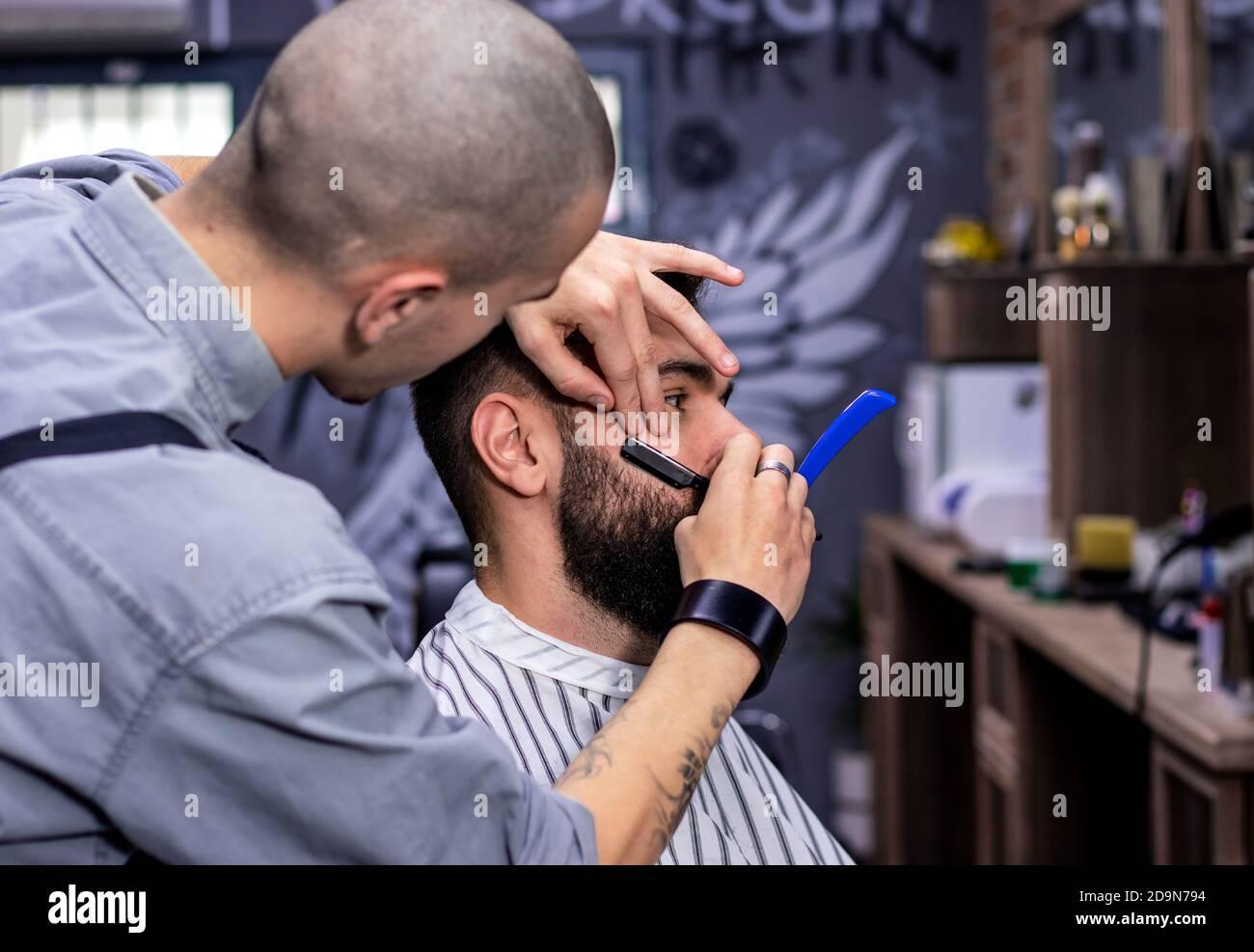 Joven hombre barbudo que se cortó el pelo por profesional en la moderna barbería. Barba y patillas afeitarse y dar forma con la navaja de afeitar clásica recta. Miembro. Foto de stock