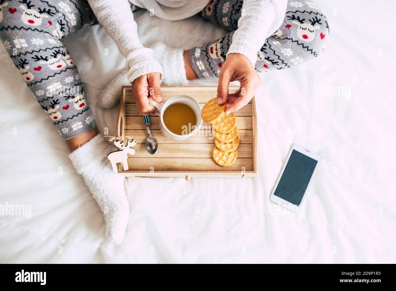 Vista superior de la mujer caucásica hacer el desayuno en la cama una cubierta blanca - decoraciones de ventana y temas - blanco fondo y navidad concepto de estilo de vida para la gente Foto de stock