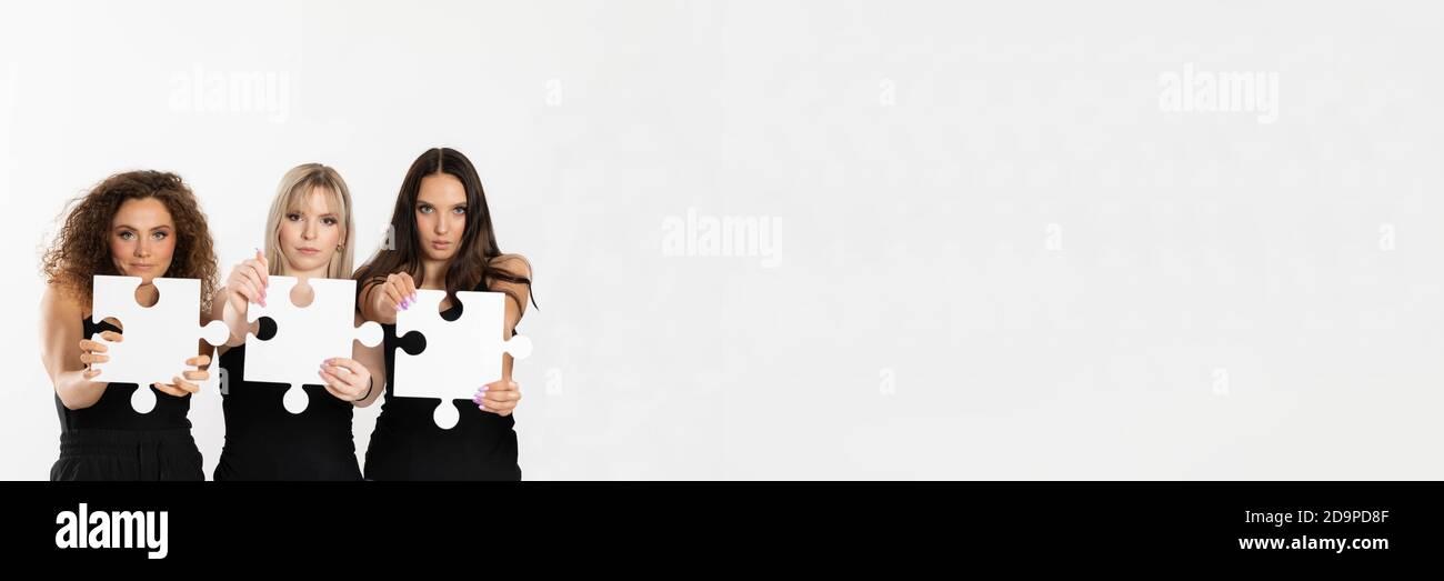 Largo panorama con espacio para una descripción con las niñas de diferentes razas con piezas de rompecabezas en la mano. Las mujeres firmes en su mensaje al mundo. Foto de stock