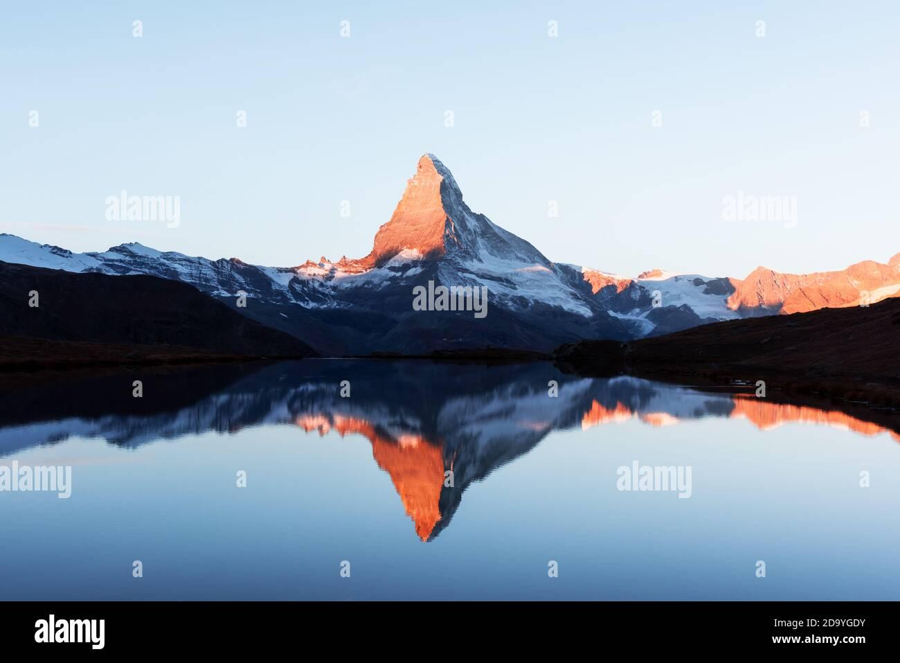 Pintoresco paisaje con coloridos Stellisee amanecer en el lago. El Matterhorn Cervino pico nevado con el reflejo en el agua clara. Zermatt, Suiza Alpes Foto de stock
