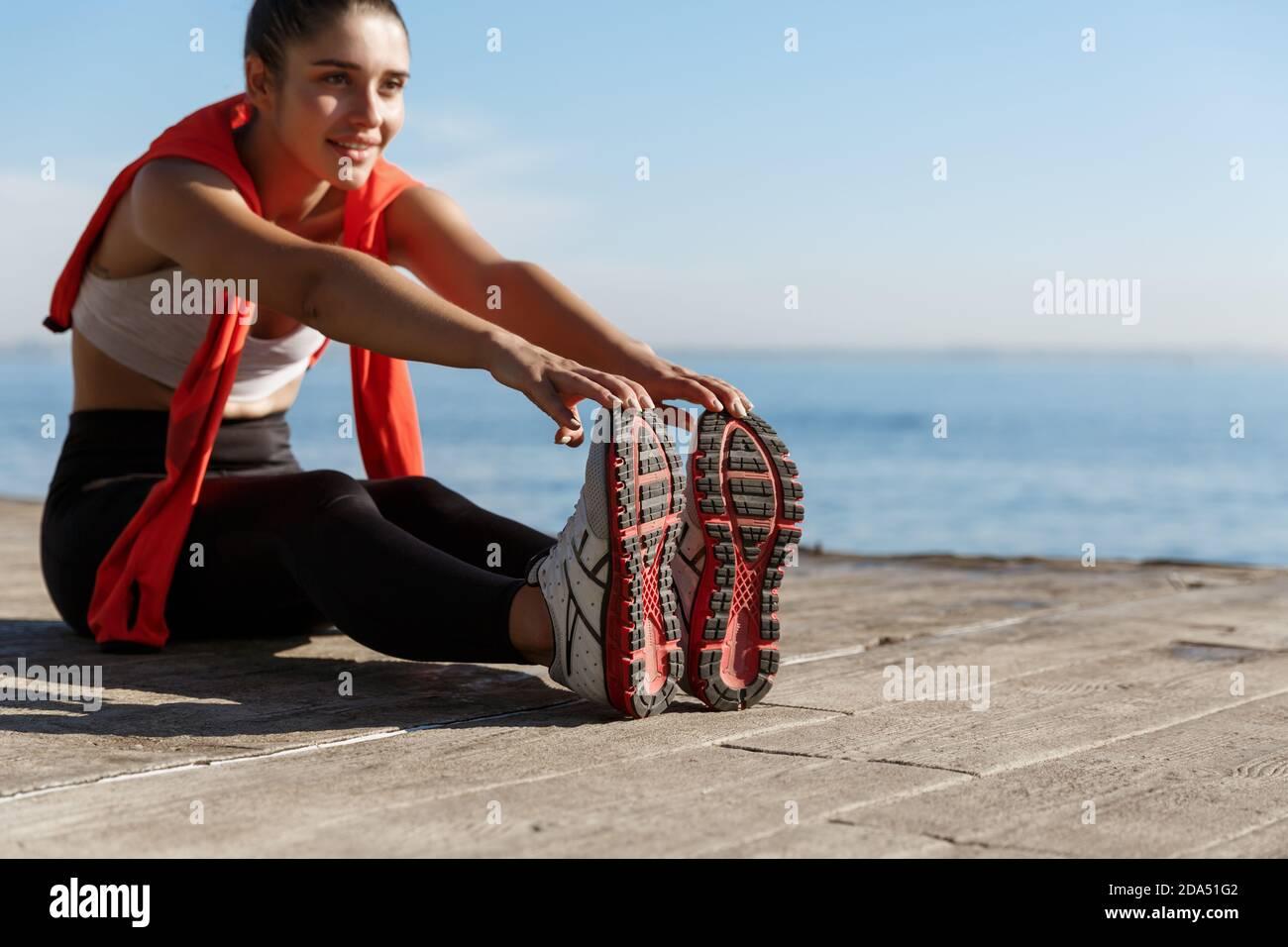 Tiro al aire libre de sonriente entrenamiento deportivo seguro cerca del mar. Mujer de fitness sentada en el muelle de madera y estirando las piernas Foto de stock