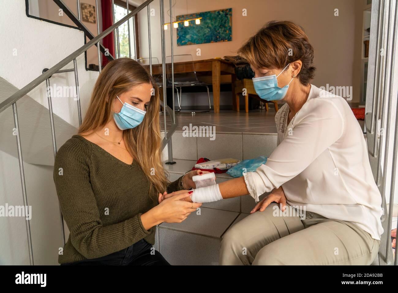 Medidas de primeros auxilios en condiciones de corona, aplicación de un vendaje, después de un accidente en el hogar, con una máscara de nariz y boca, al dar primeros auxilios Foto de stock