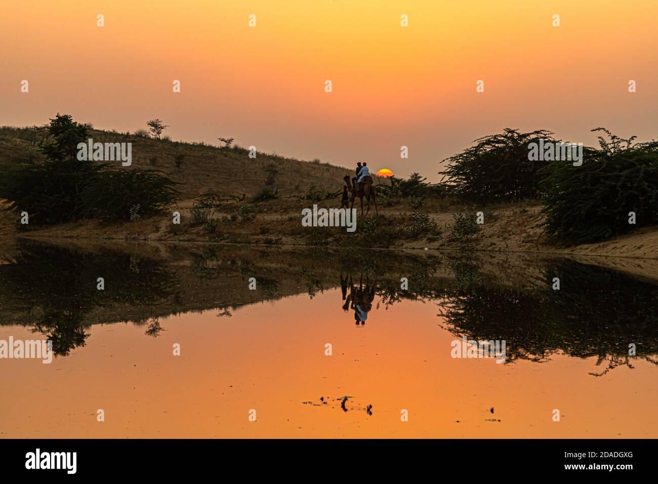 vista de la hermosa puesta de sol y el reflejo de camello en el estanque. Foto de stock