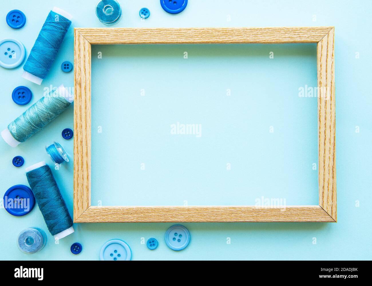 Bobinas de hilo y botones en tonos azules en un fondo azul Foto de stock