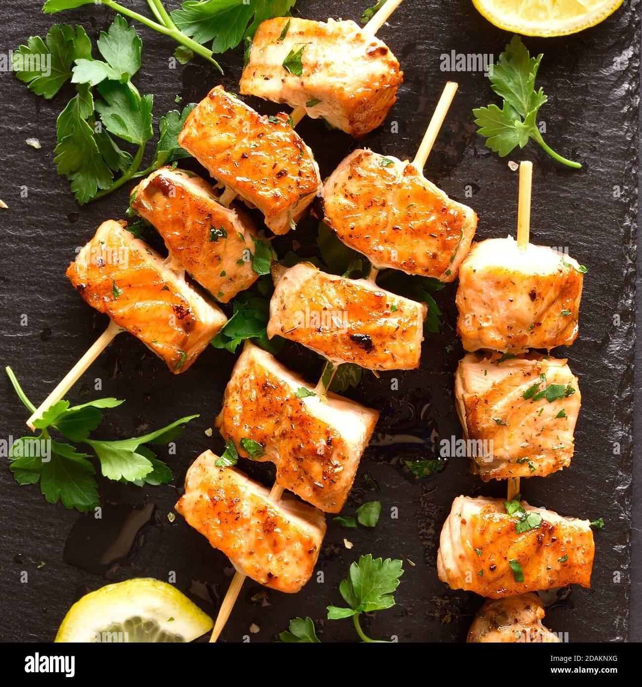 Vista de cerca del kebab de salmón a la parrilla. Brochetas de salmón a la barbacoa sobre pizarra de piedra. Vista superior, disposición plana Foto de stock