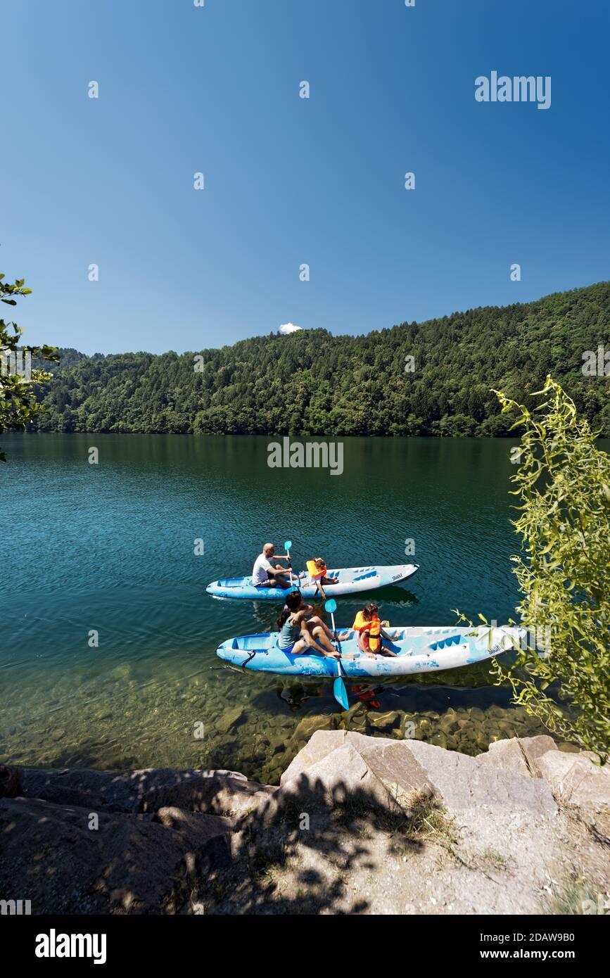 Familia con dos niños en dos kayaks en el hermoso Lago Levico en Valsugana (Valle de Sugana), Trentino Alto Adige, Italia, Europa Foto de stock