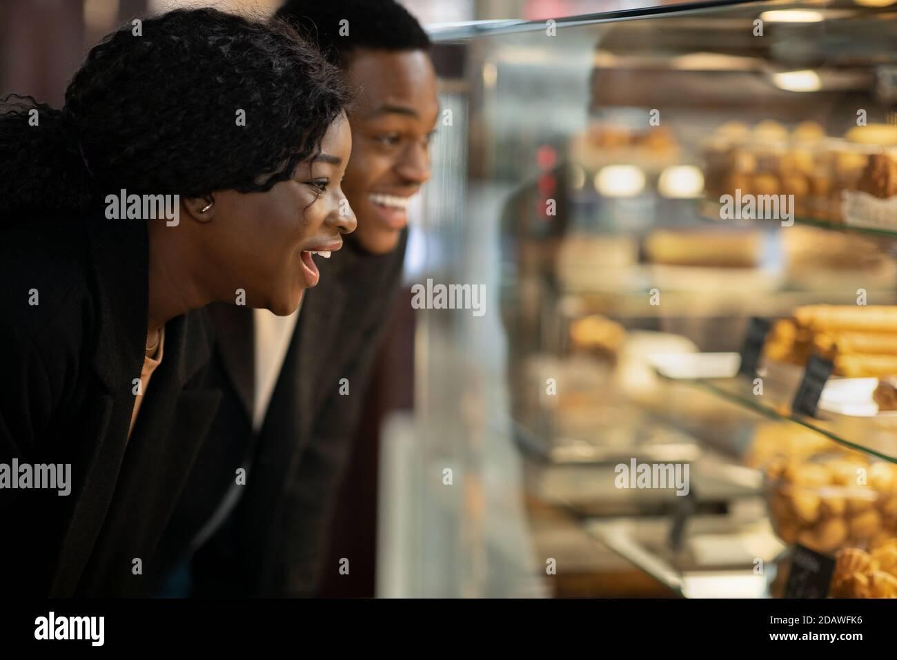 Sorprendida feliz mujer milenaria y hombre de pie en frente de escaparate de cristal con pasteles y pasteles Foto de stock