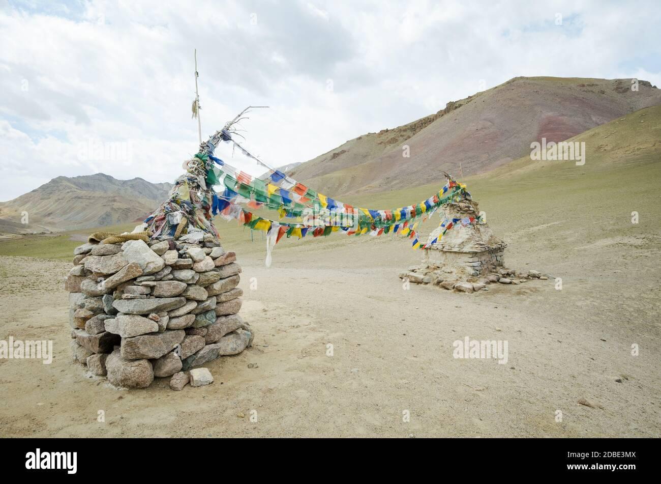 Banderas de hito y estilo tibetano sobre un camino en la sierra de Ladak, India Foto de stock