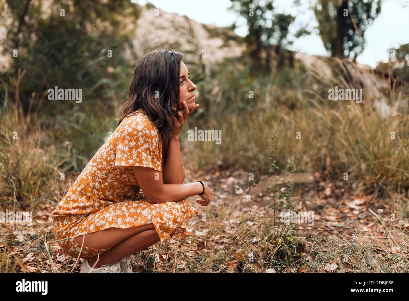 Pensativa hermosa mujer morena con un vestido sentándose en el bosques Foto de stock
