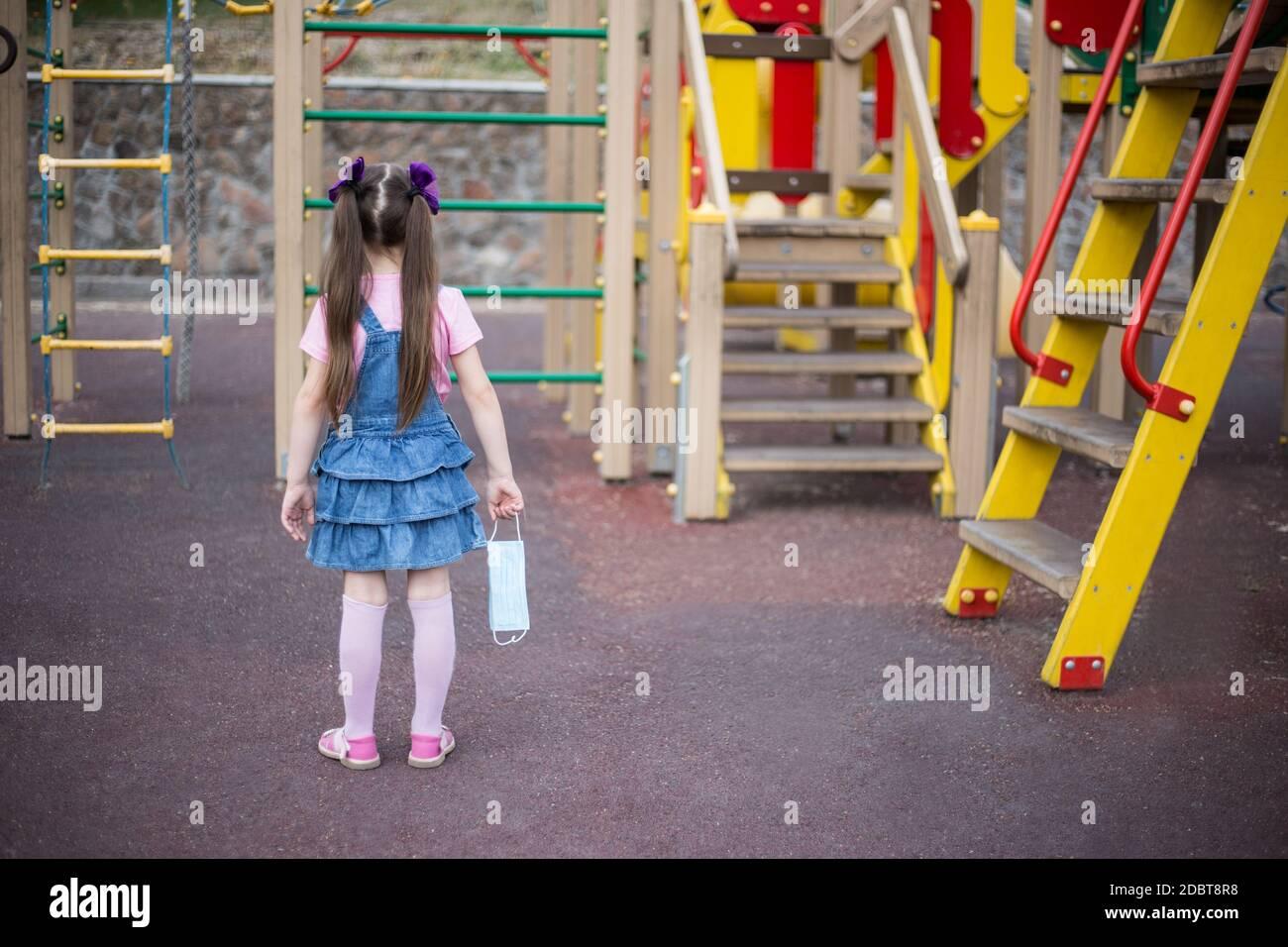 La chica está sola en el patio de recreo, porque el aislamiento y la cuarentena Foto de stock
