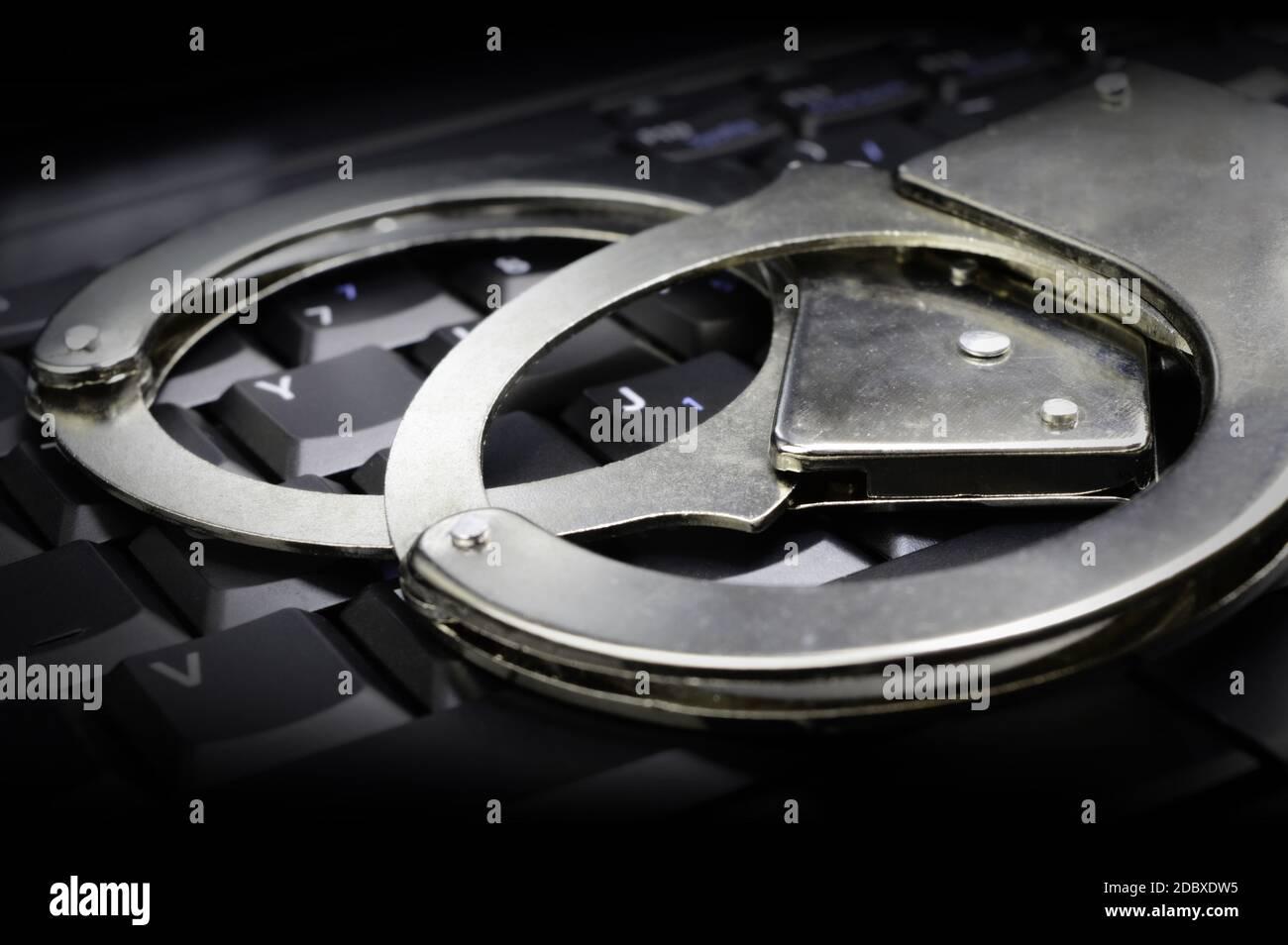 Una imagen conceptual con esposas de acero para la aplicación de la ley colocadas encima de un teclado oscuro para los sistemas legales en línea en orden. Foto de stock