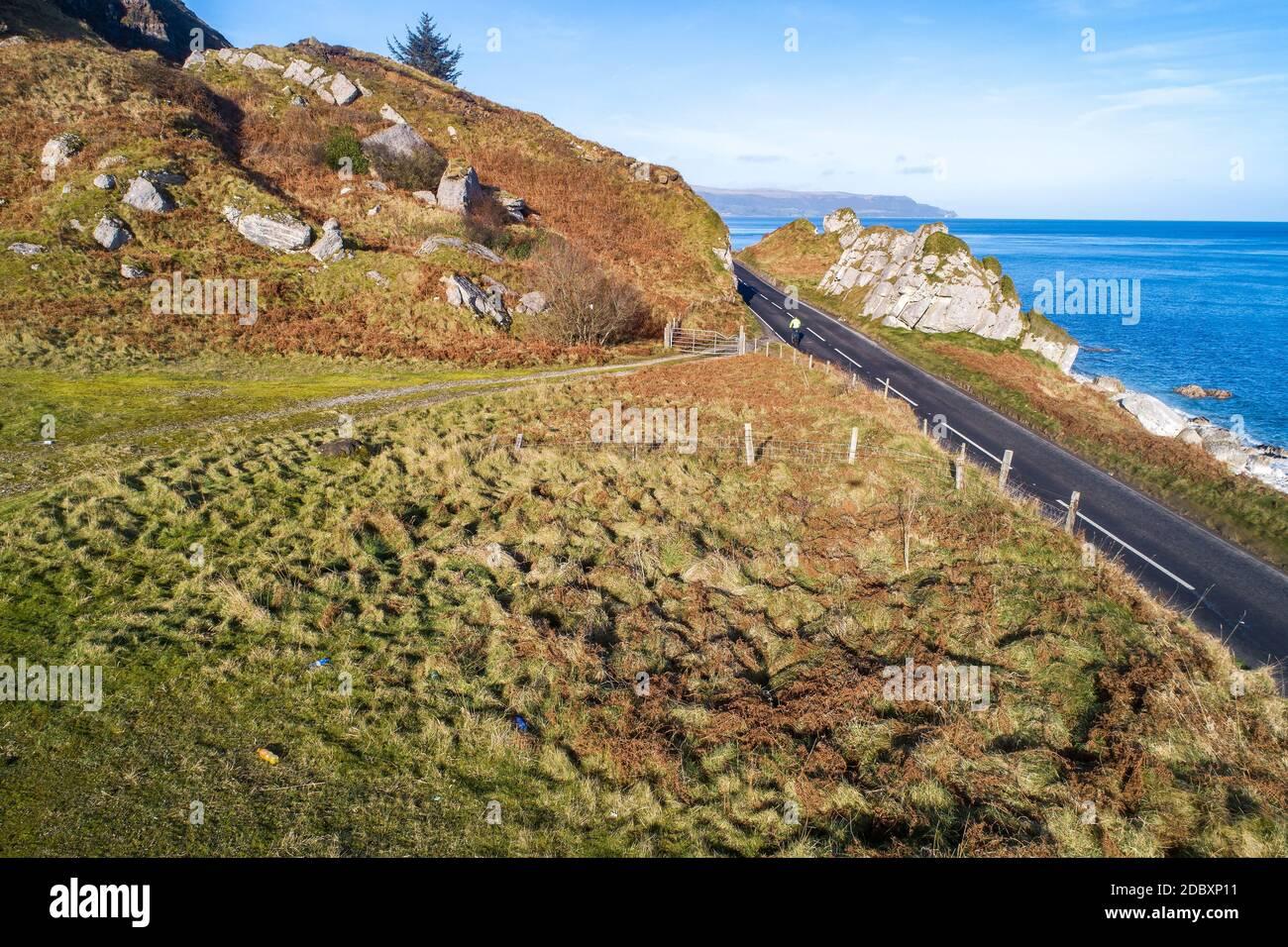 La costa oriental de Irlanda del Norte y la Ruta Costera Causeway con un ciclista. Una de las carreteras costeras más pintorescas de Europa. Vista aérea en invierno Foto de stock