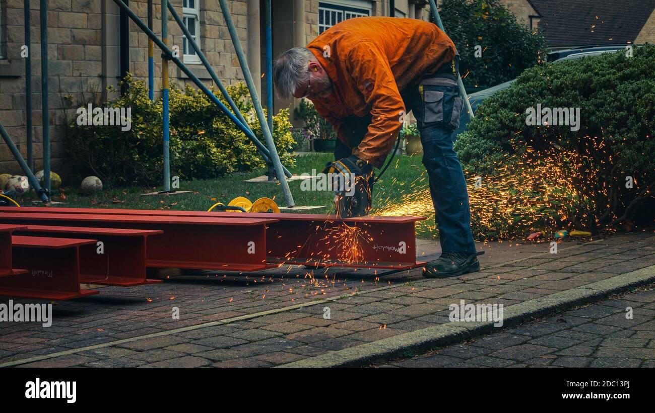 Trabajador con ropa protectora cortando a través de acero RSJ con una sierra de metal circular creando chispas en un sitio de construcción doméstica, Inglaterra Foto de stock