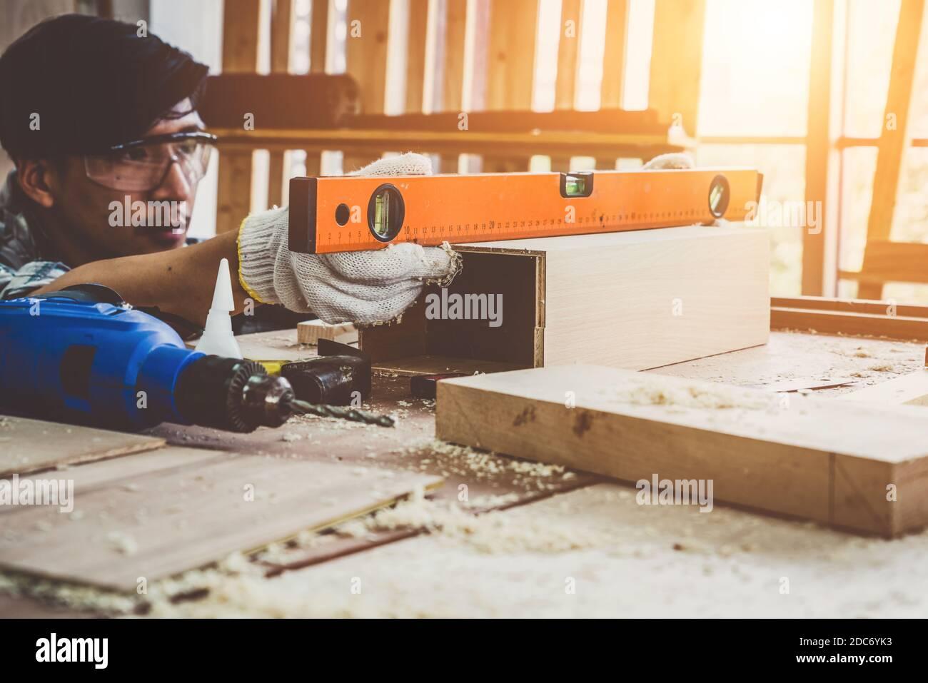 Carpintero trabajando en artesanía de madera en el taller para producir material de construcción o muebles de madera. El joven carpintero asiático utiliza herramientas profesionales para Foto de stock