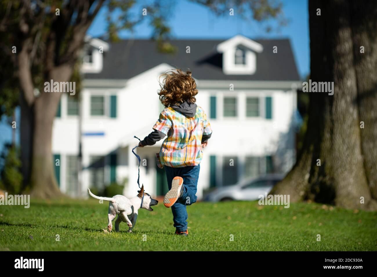 Niño con su mascota corre a la carrera. Foto de stock