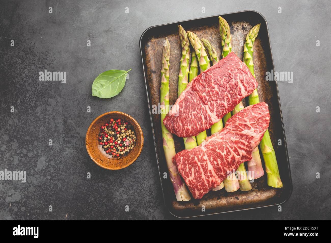 Filete crudo con espárragos verdes en bandeja sobre fondo negro, vista superior Foto de stock