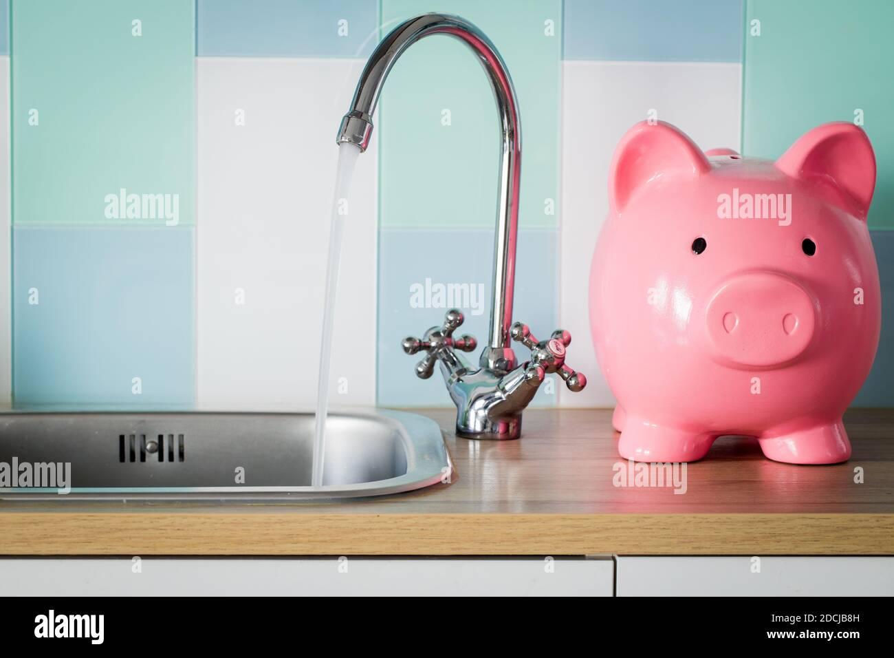 El agua corriente y un banco de pigmeos de pie junto a ella. Concepto de precio de consumo de agua Foto de stock