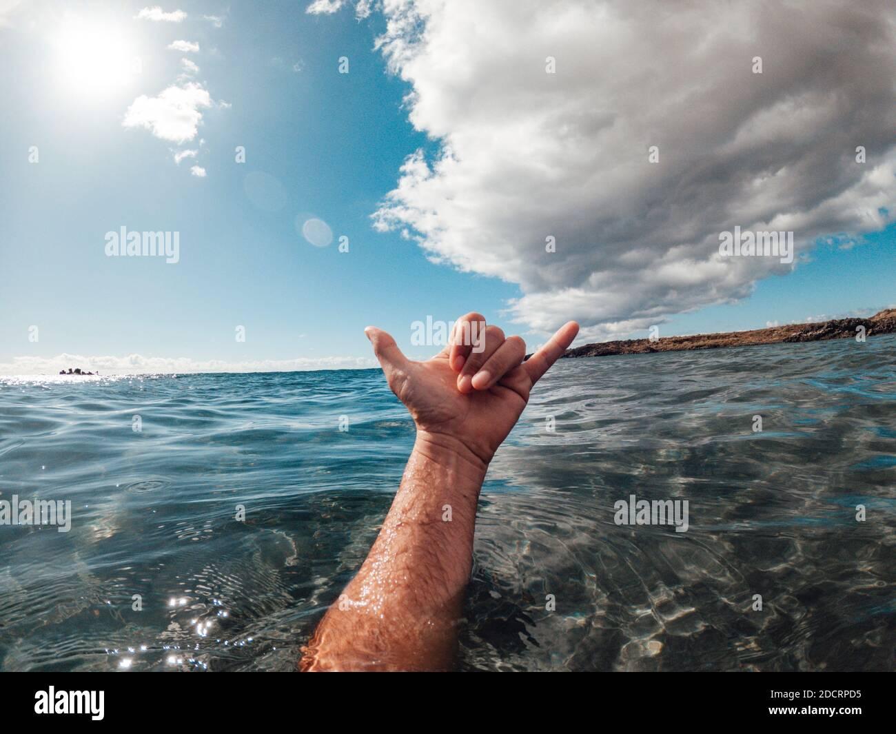 Hombre manos en el surf signo hallo fuera del azul agua del océano con la costa y el cielo agradable en el fondo - concepto de personas y vacaciones de verano Foto de stock