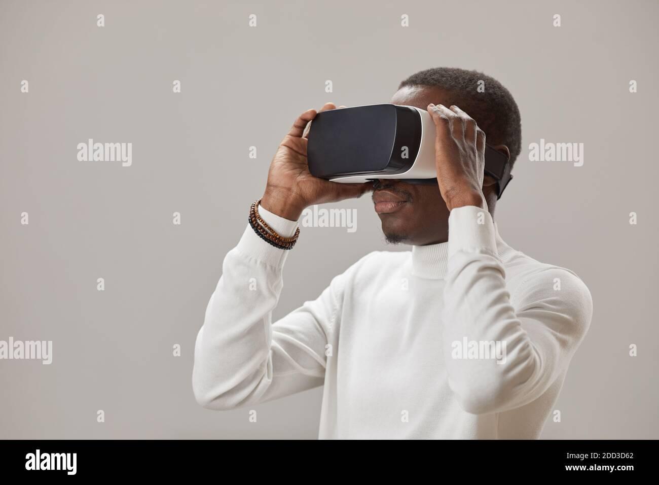 Joven africano en gafas virtuales jugando en realidad virtual juego contra el fondo gris Foto de stock