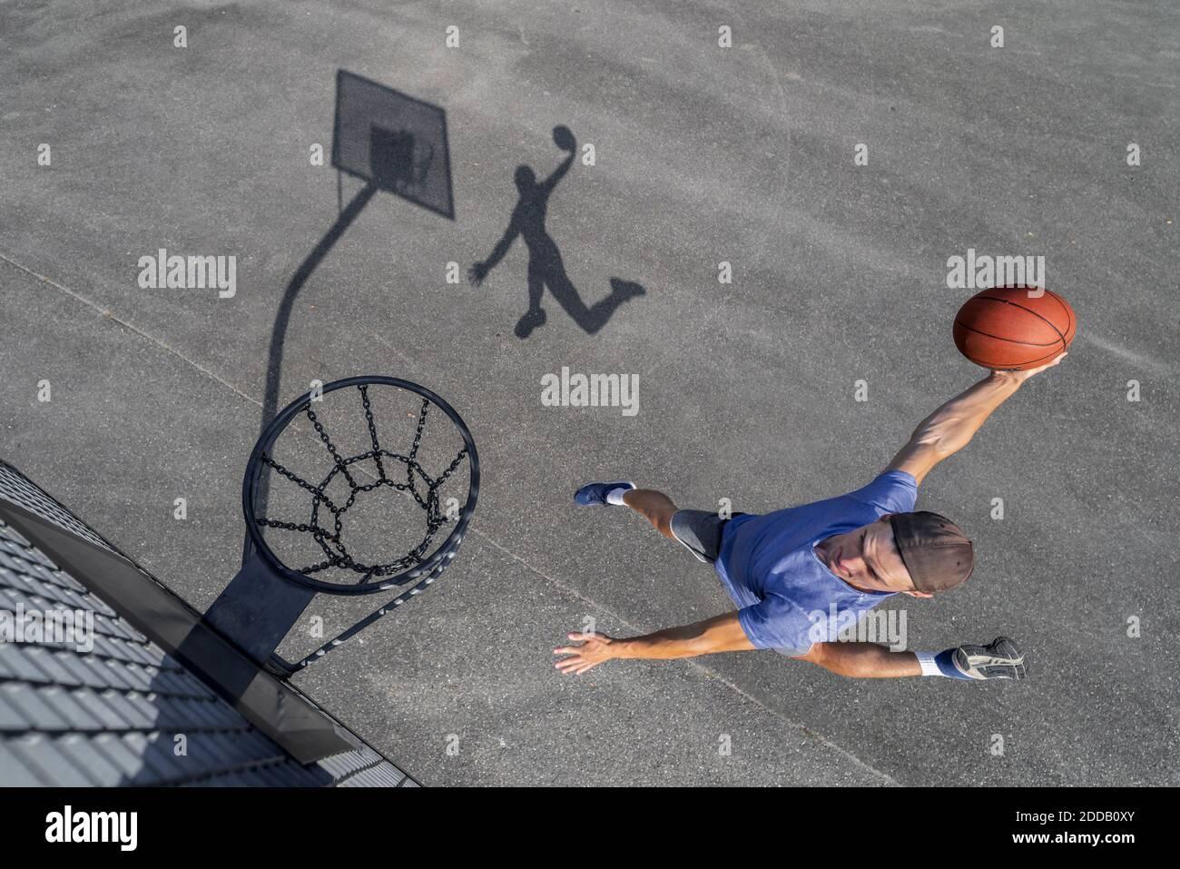 Joven hombre dunking pelota en el aro mientras juega al baloncesto día soleado Foto de stock